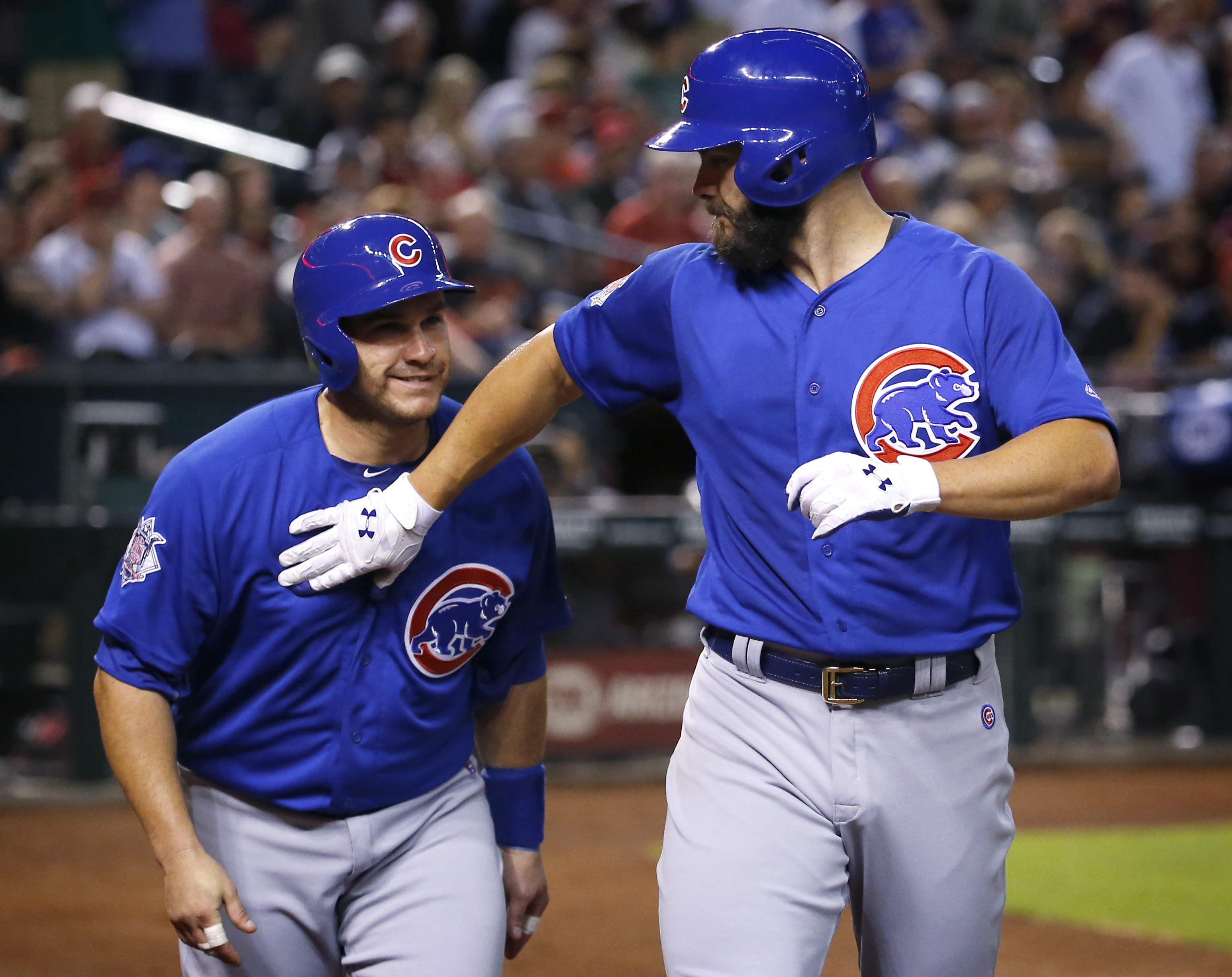 Chicago Cubs Jake Arrieta, right, greets teammate Miguel Montero at the plate after hitting a two-run home run against the Arizona Diamondbacks during the second inning of a baseball game, Sunday, April 10, 2016, in Phoenix. (AP Photo/Matt York)