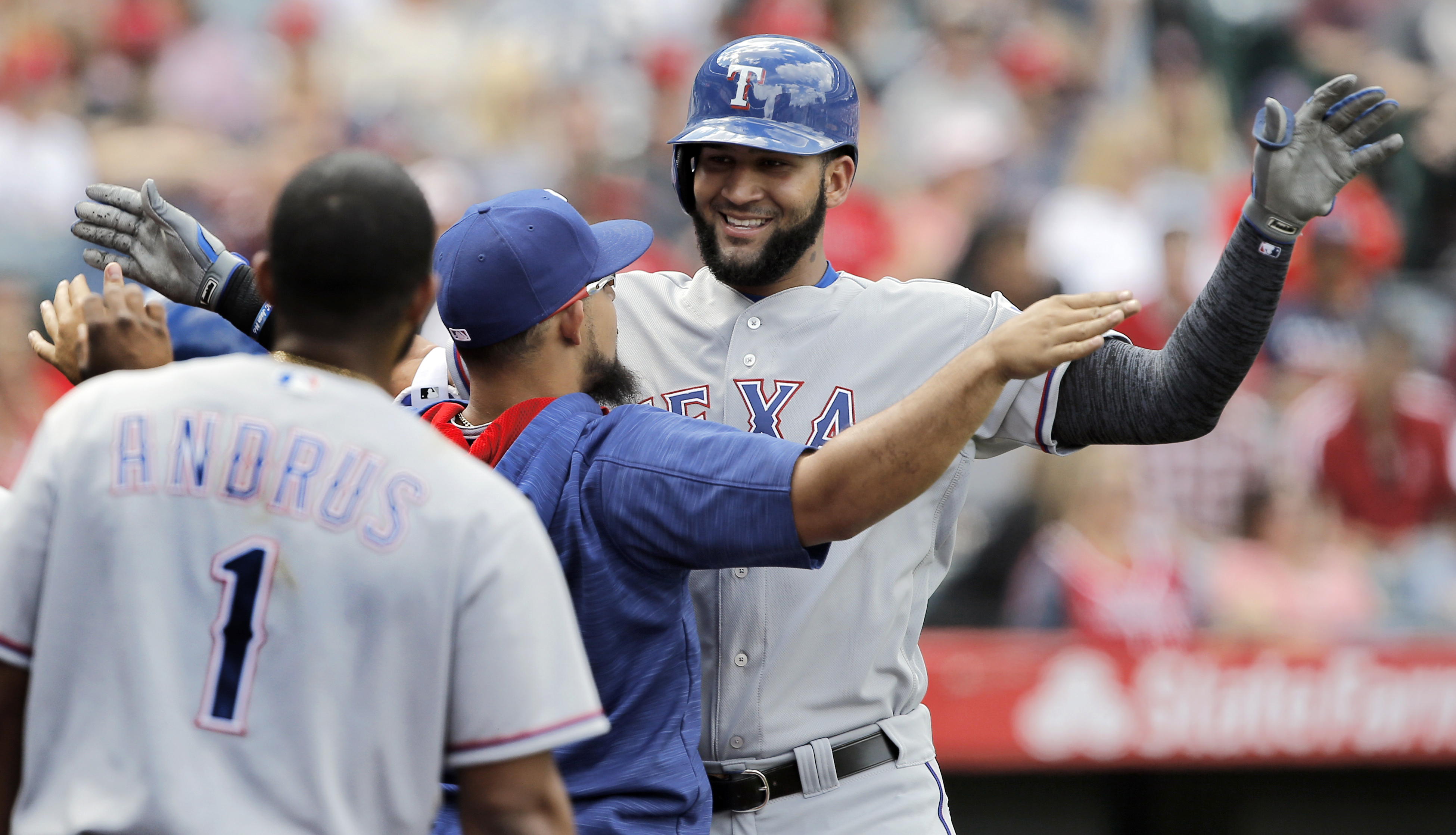 Texas Rangers' Nomar Mazara, right, gets congratulations from teammate Rougned Odor, center, after hitting a solo home run against the Los Angeles Angels during the fifth inning of a baseball game in Anaheim, Calif., Sunday, April 10, 2016. (AP Photo/Alex