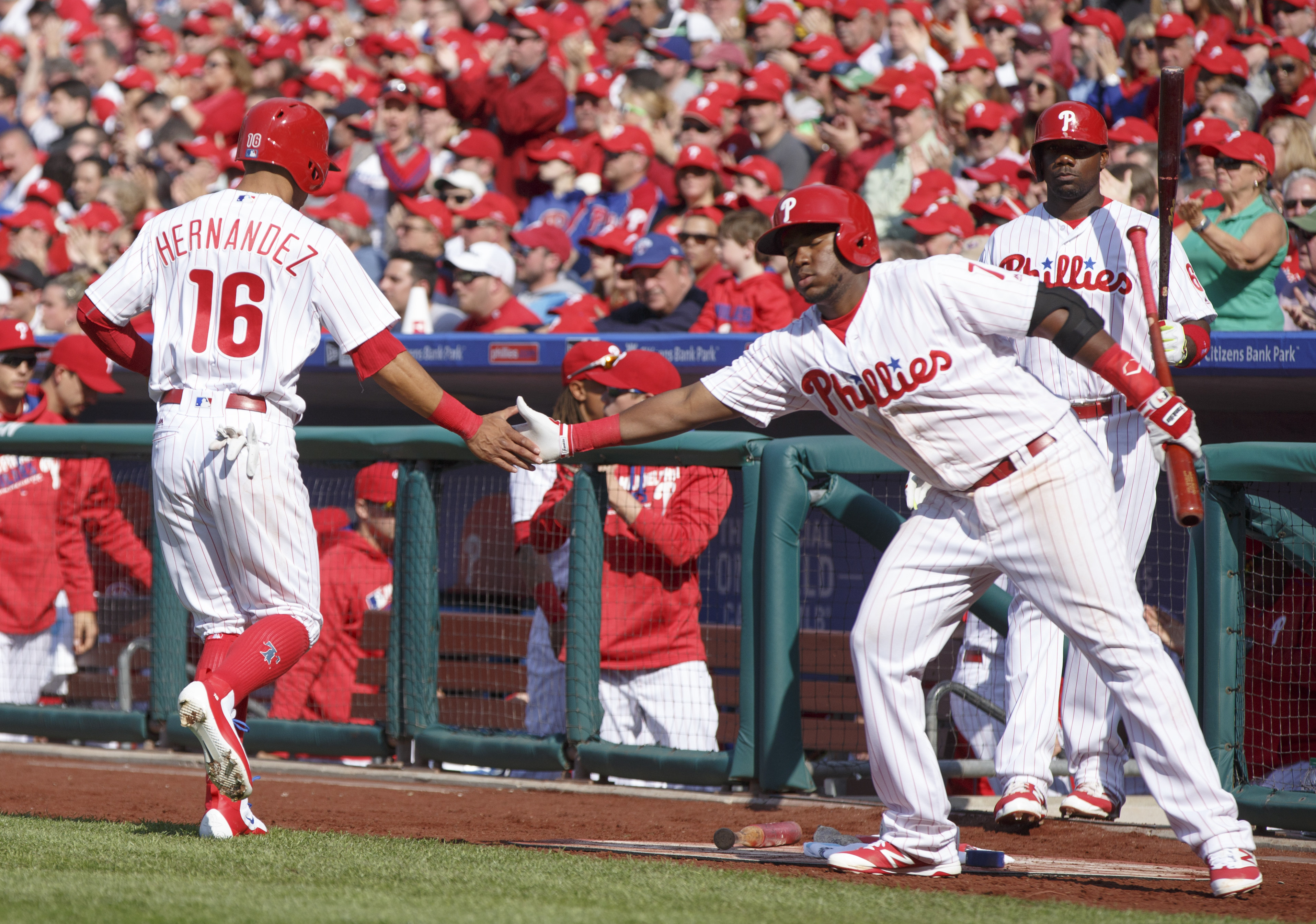 Philadelphia Phillies' Maikel Franco (7) reaches out to congratulate Cesar Hernandez (16) on scoring a run on the single by Odubel Herrera during the first inning of an opening day baseball game against the San Diego Padres, Monday, April 11, 2016, in Phi