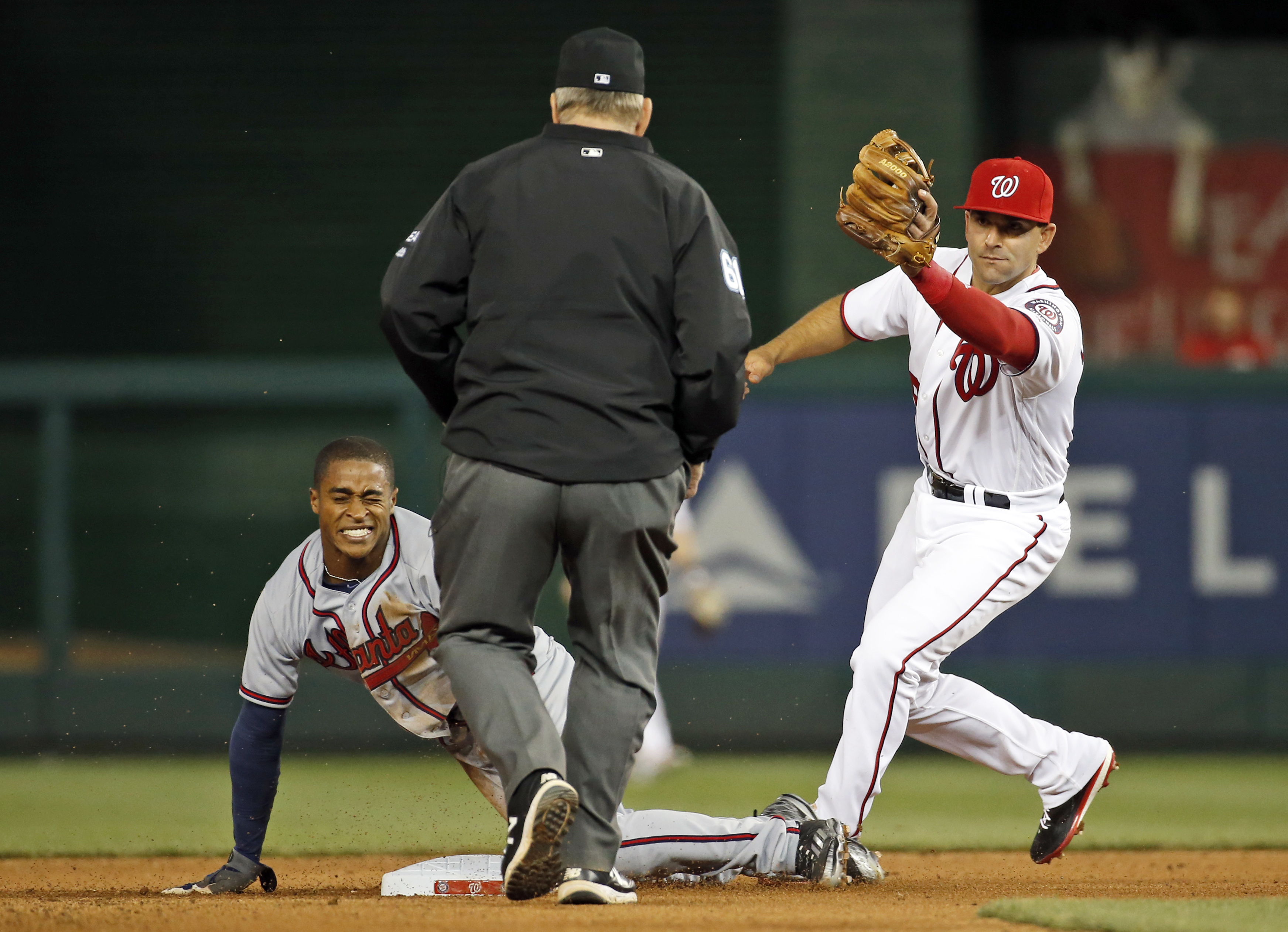 Washington Nationals second baseman Danny Espinosa, right, holds up his glove with the ball in it after making a tag on Atlanta Braves' Mallex Smith for the out on the steal attempt of second base during the fourth inning of a baseball game at Nationals P