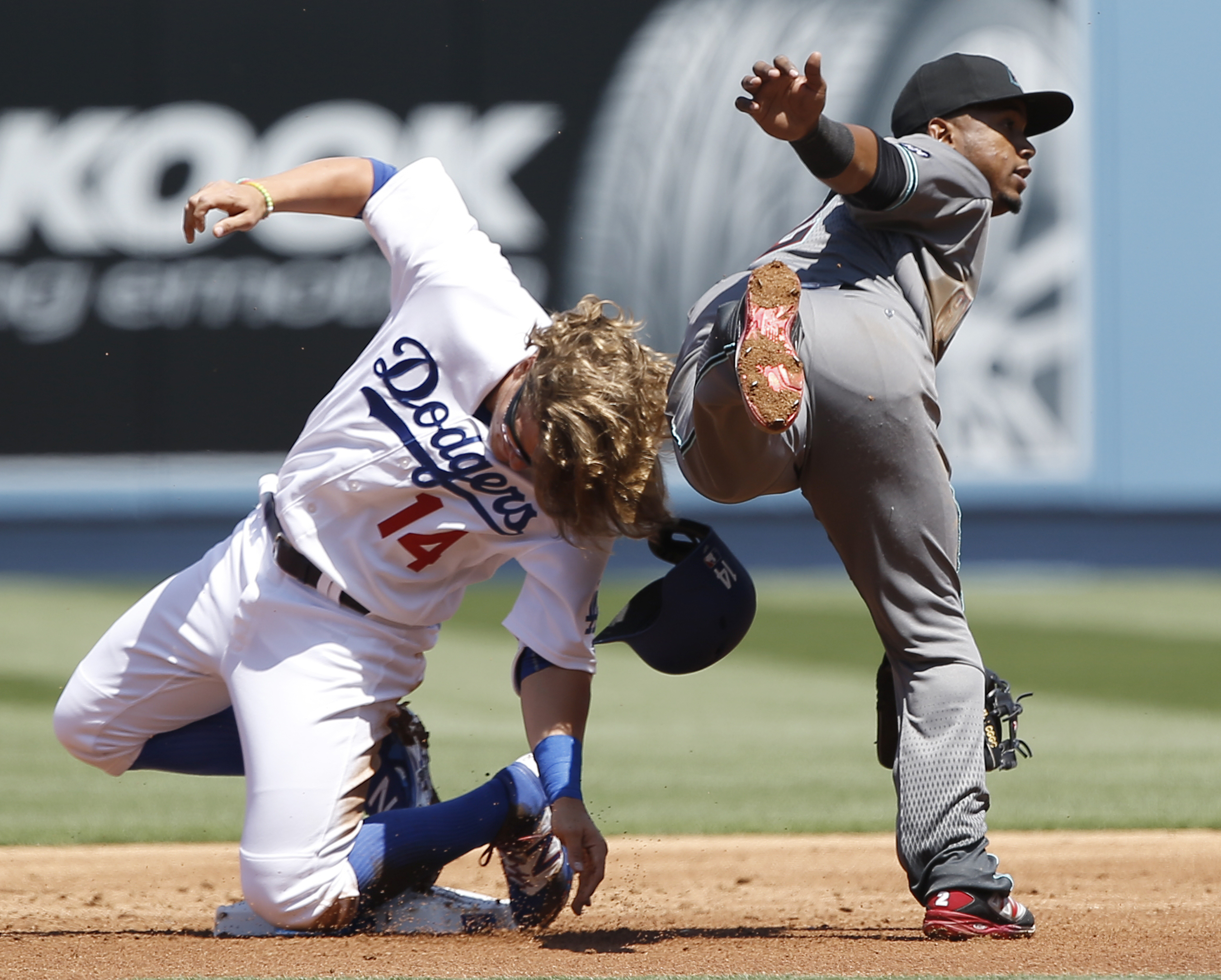 Arizona Diamondbacks second baseman Jean Segura, right, leaps after forcing out Los Angeles Dodgers Enrique Hernandez (14), to make the relay to first, but not in time to get Yasiel Puig during the first inning of a baseball game in Los Angeles, Tuesday,