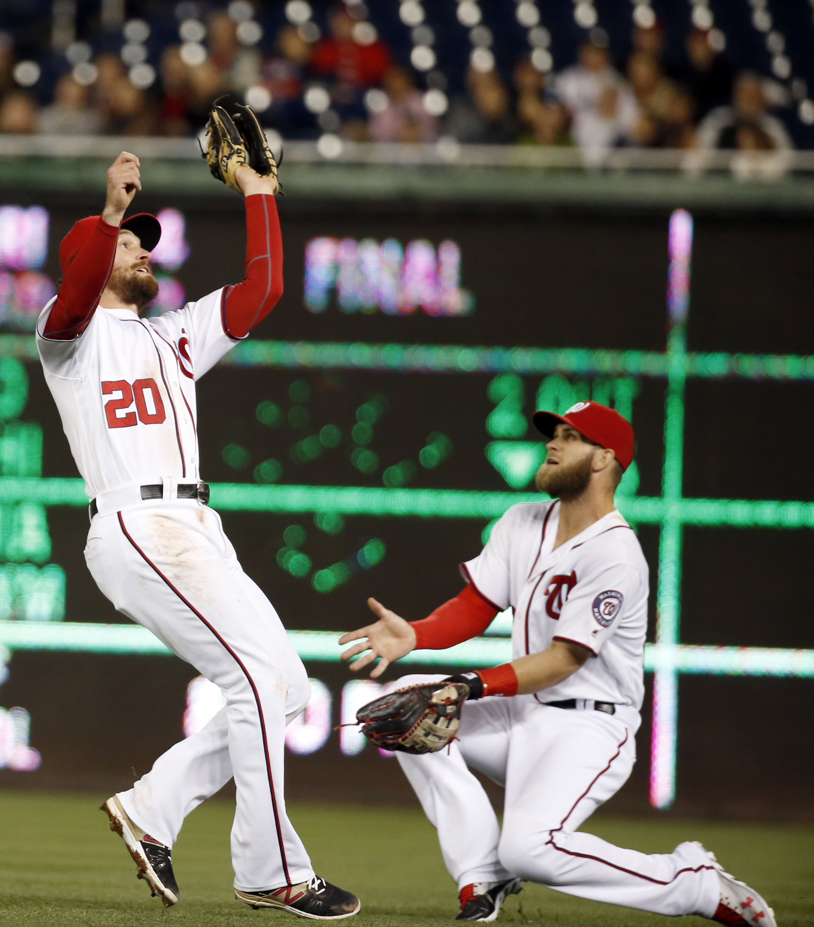 Washington Nationals second baseman Daniel Murphy (20) catches a ball hit by Atlanta Braves' Jhoulys Chacin, with Nationals right fielder Bryce Harper (34) nearby, during the fifth inning of a baseball game at Nationals Park, Tuesday, April 12, 2016, in W