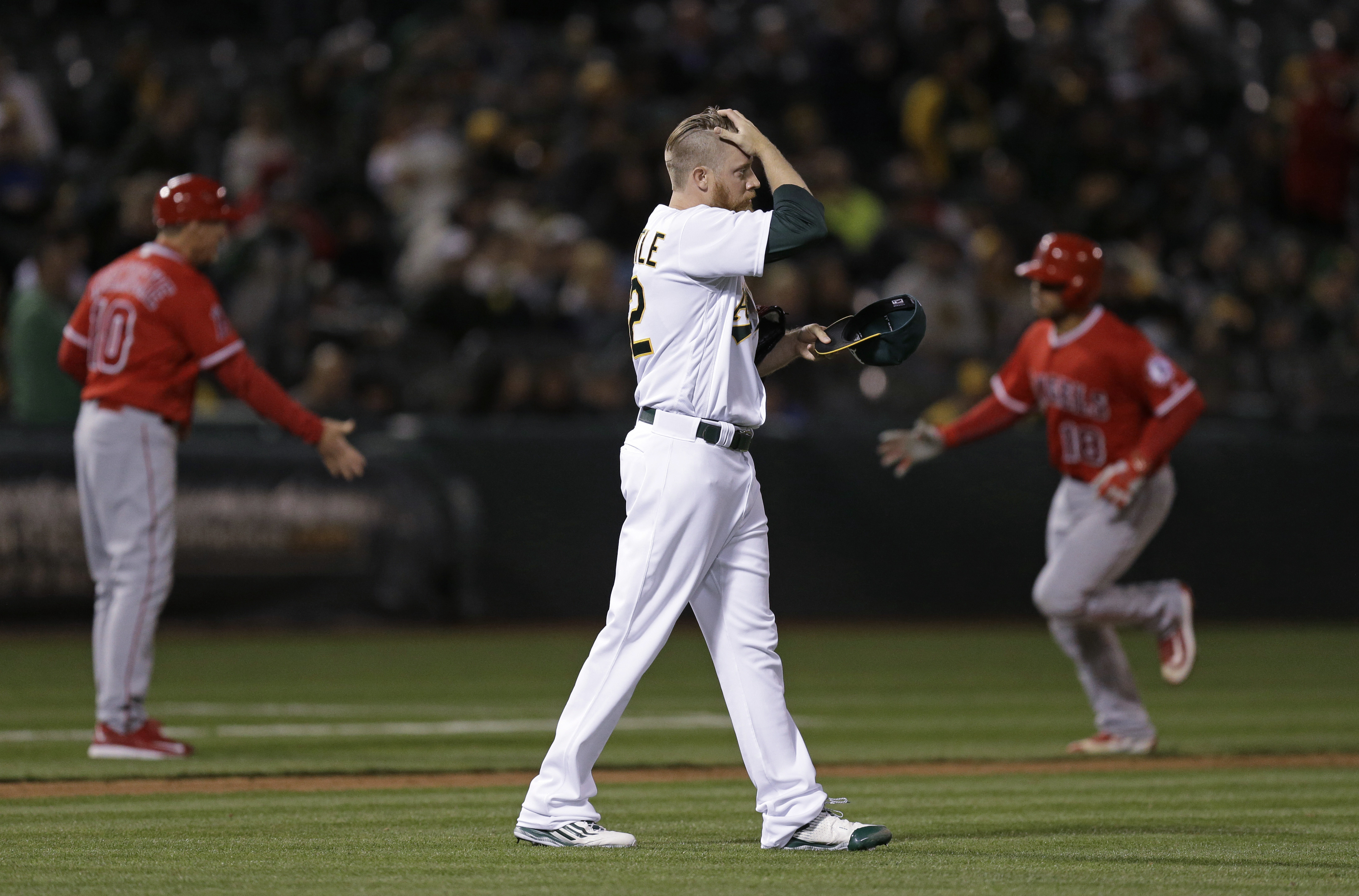 Oakland Athletics' Sean Doolittle places his hand to his head after giving up a two-run home run to Los Angeles Angels' Geovany Soto, right, during the ninth inning of a baseball game Tuesday, April 12, 2016, in Oakland, Calif. (AP Photo/Ben Margot)