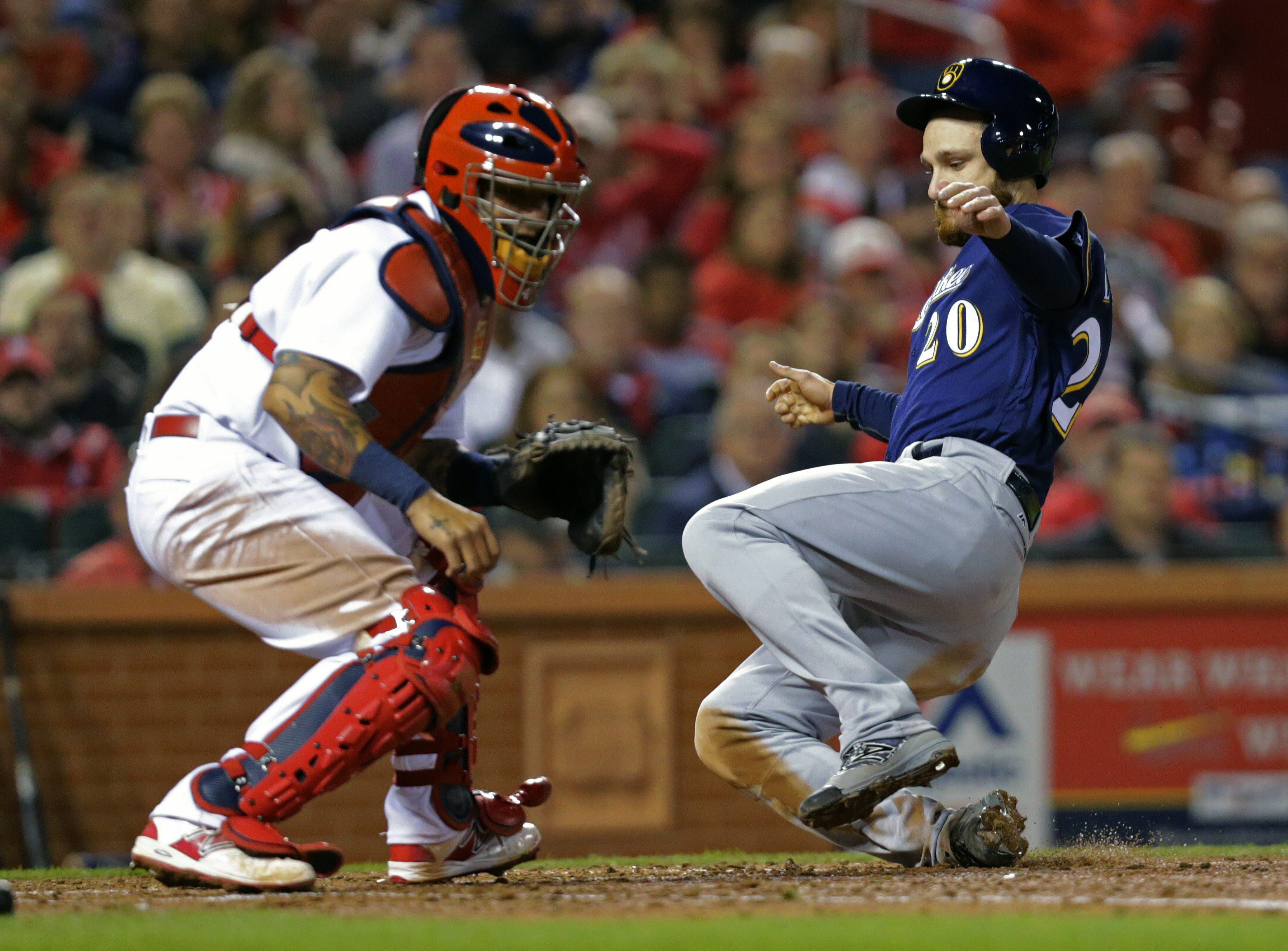 Milwaukee Brewers' Jonathan Lucroy (20) scores from first on a double by Chris Carter as St. Louis Cardinals catcher Yadier Molina (4) waits for a throw in the fifth inning of a baseball game, Wednesday, April 13, 2016 in St. Louis. (AP Photo/Tom Gannam)