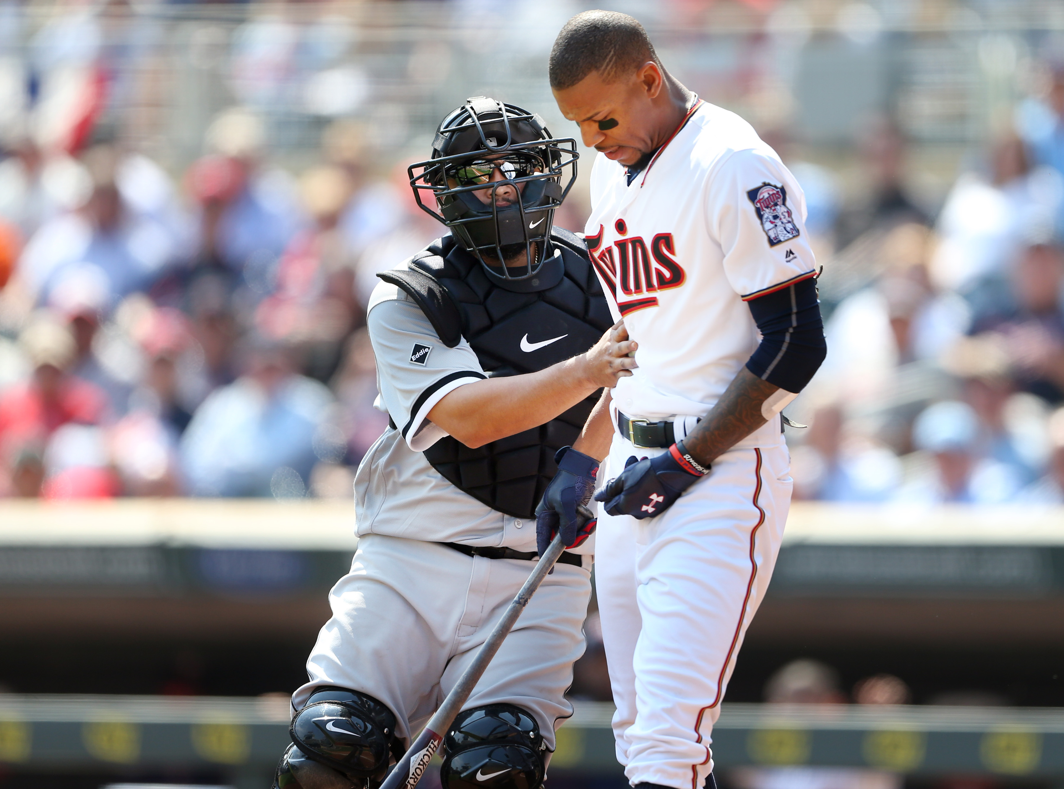 Chicago White Sox catcher Dioner Navarro assists Minnesota Twins' Byron Buxton  after Buxton was hit by a pitch thrown by Mat Latos in the third inning of a baseball game at Target Field, Thursday April 14, 2016, in Minneapolis, Minn. (Jerry Holt Jerry/St