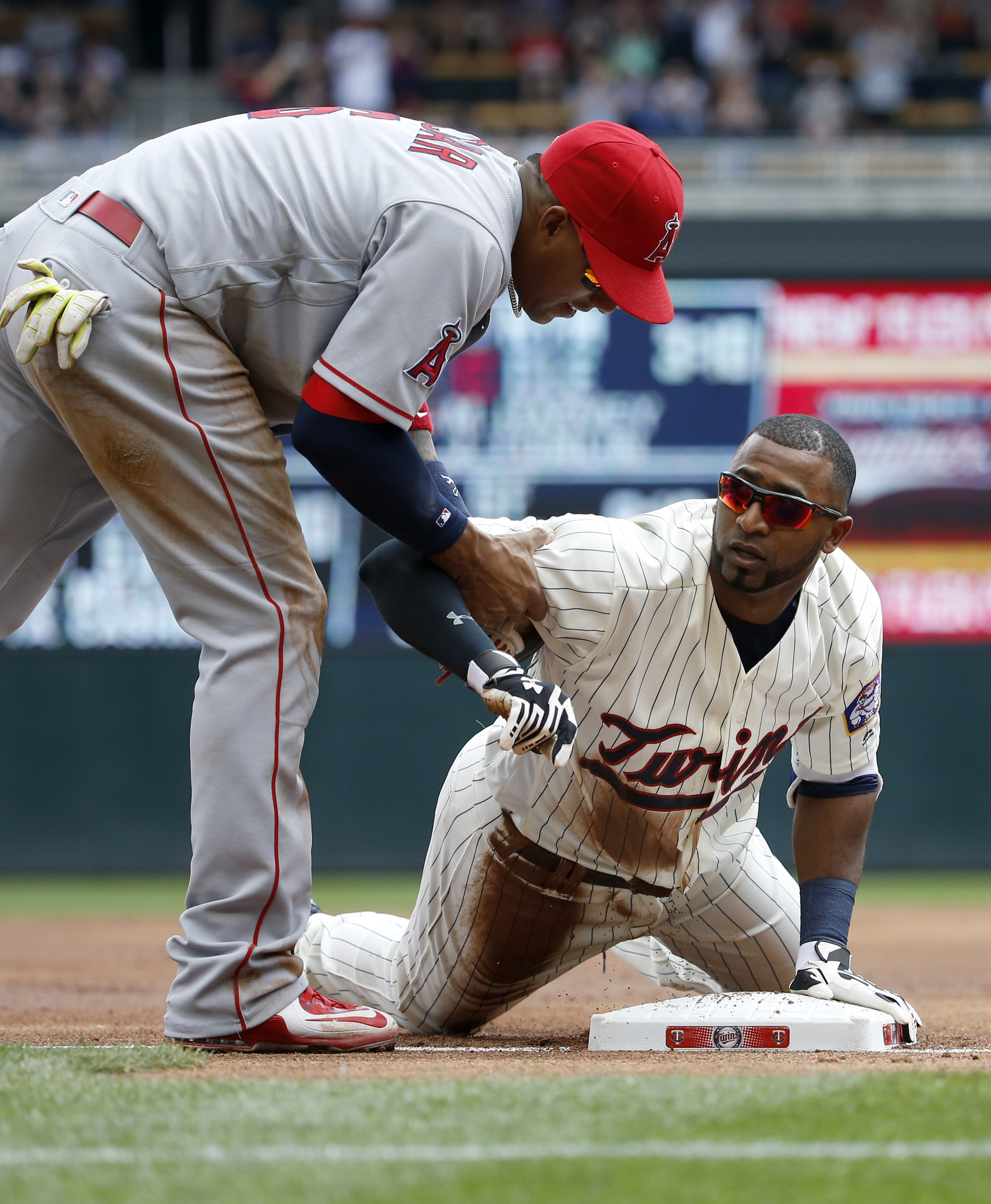 Los Angeles Angels third baseman Yunel Escobar (6) helps Minnesota Twins'  Eduardo Nunez after Nunez made it safely to third on a triple during the first inning of a baseball game in Minneapolis, Saturday, April 16, 2016. (AP Photo/Ann Heisenfelt)