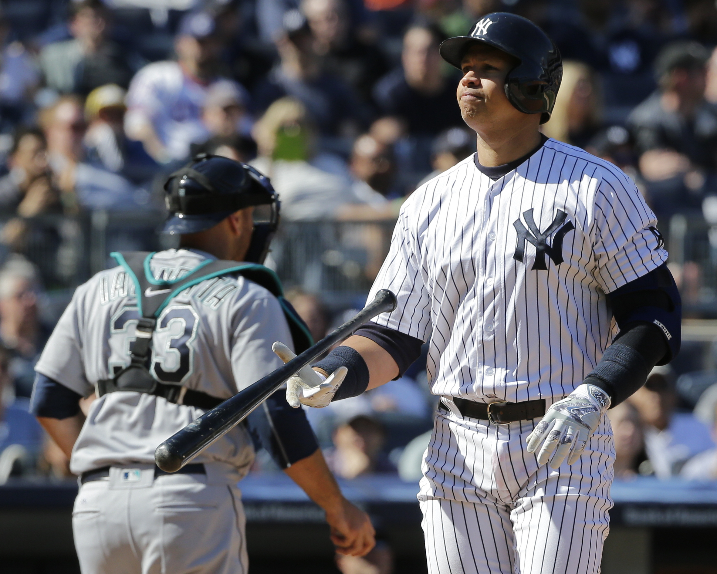 New York Yankees' Alex Rodriguez flips his bat after striking out during the sixth inning of a baseball game as Seattle Mariners catcher Chris Iannetta (33) walks toward the dugout Saturday, April 16, 2016, in New York. (AP Photo/Frank Franklin II)