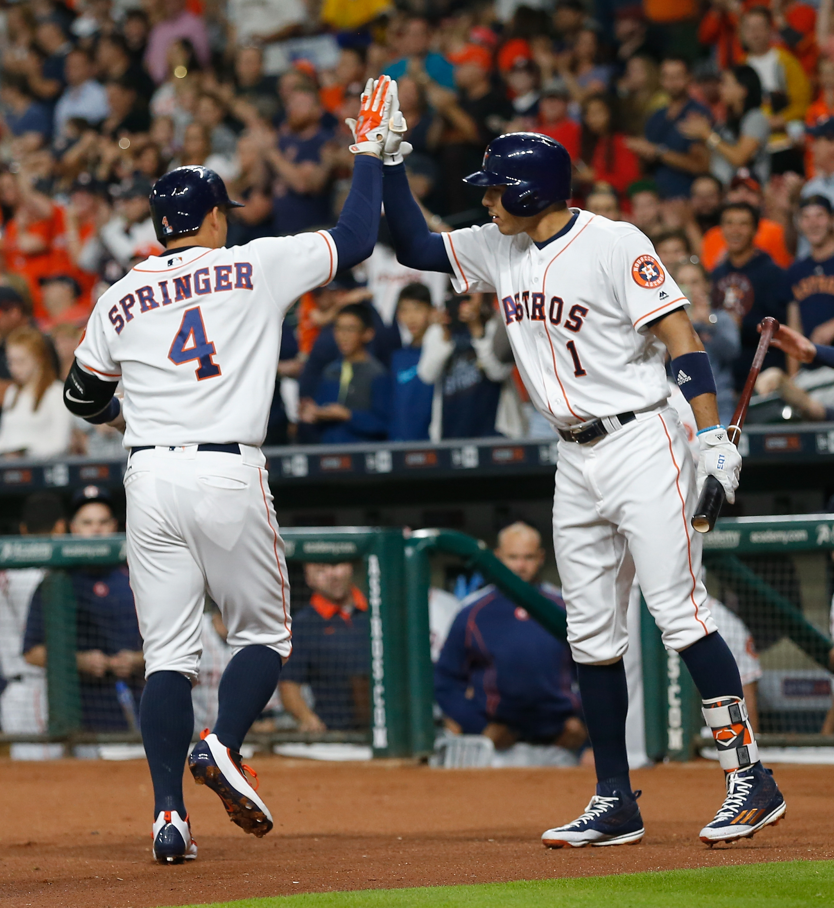 Houston Astros' George Springer (4) receives a high-five from Carlos Correa (1) after hitting a home run against the Detroit Tigers duirng the first inning of a baseball game, Saturday, April 16, 2016, in Houston.  (AP Photo/Bob Levey)