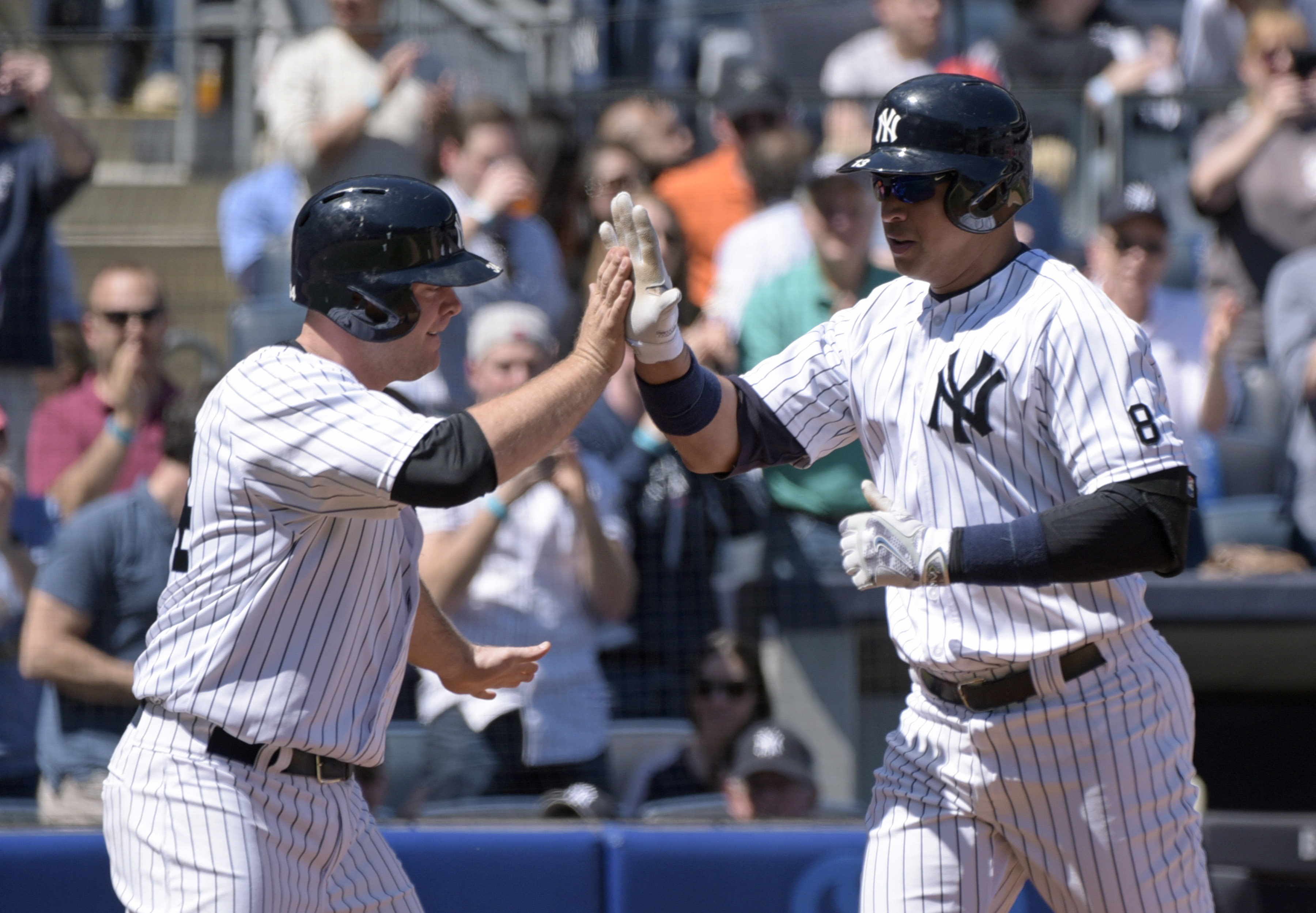New York Yankees' Alex Rodriguez, right, celebrates with Brian McCann after hitting a two-run home run, also scoring McCann, during the second inning of a baseball game against the Seattle Mariners, Sunday, April 17, 2016, at Yankee Stadium in New York. (