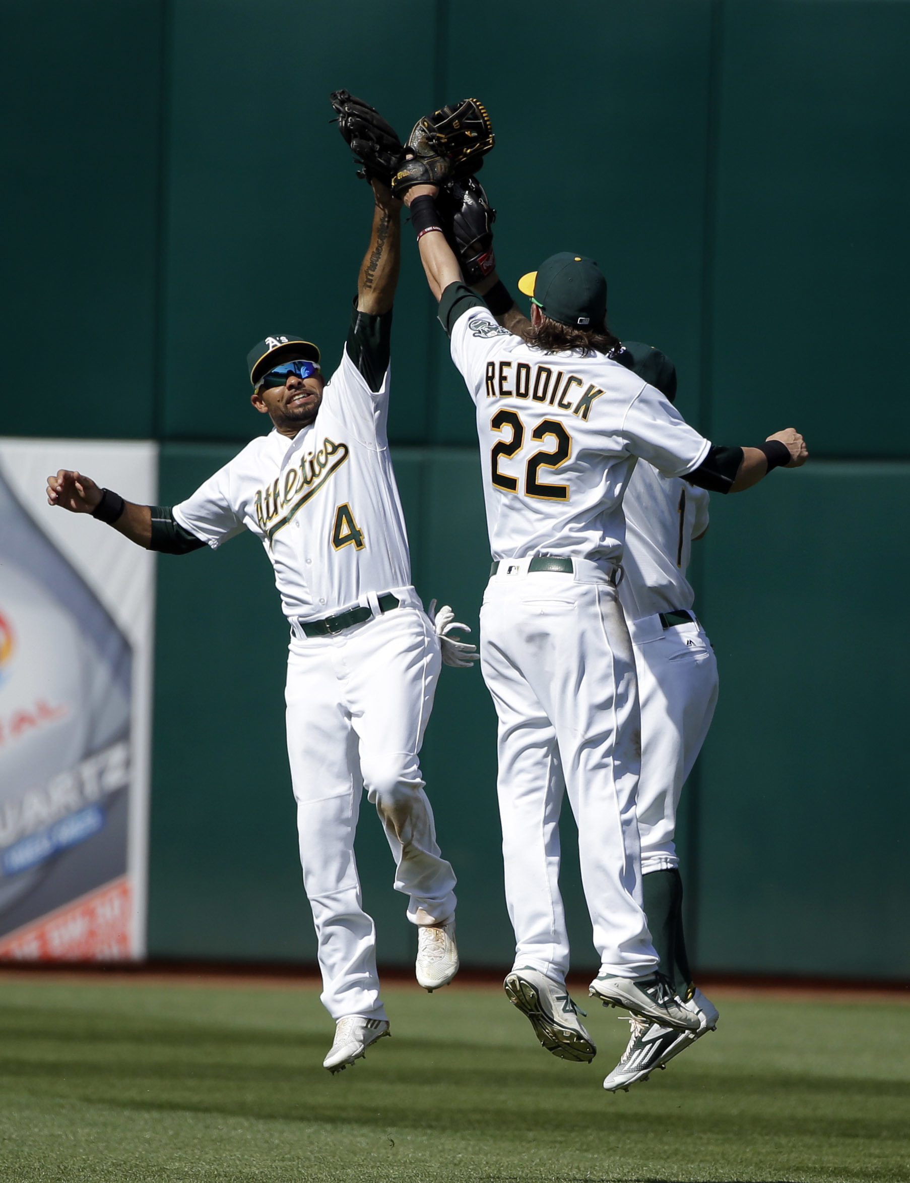 Oakland Athletics' Josh Reddick (22) and Coco Crisp (4) celebrate after a 3-2 win over the Kansas City Royals during a baseball game Sunday, April 17, 2016, in Oakland, Calif. (AP Photo/Marcio Jose Sanchez)