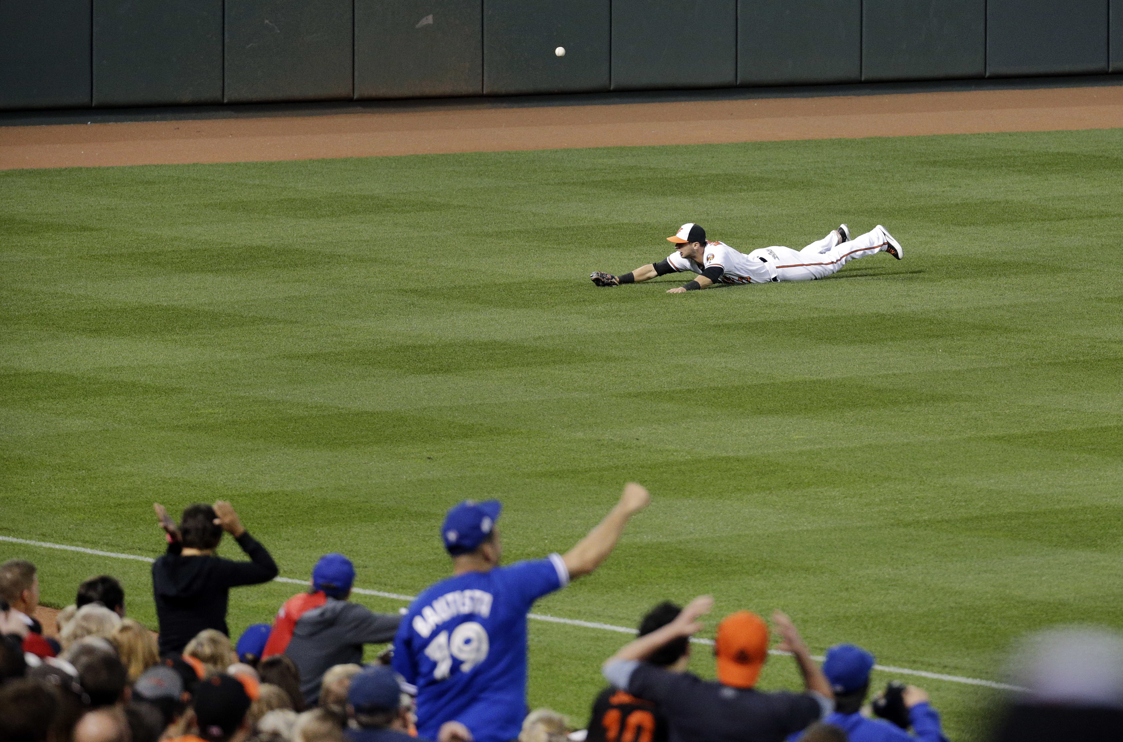 Fans react as a fly ball double by Toronto Blue Jays' Troy Tulowitzki gets past Baltimore Orioles left fielder Joey Rickard in the third inning of a baseball game in Baltimore, Tuesday, April 19, 2016. Michael Saunders and Jose Bautista scored on the play