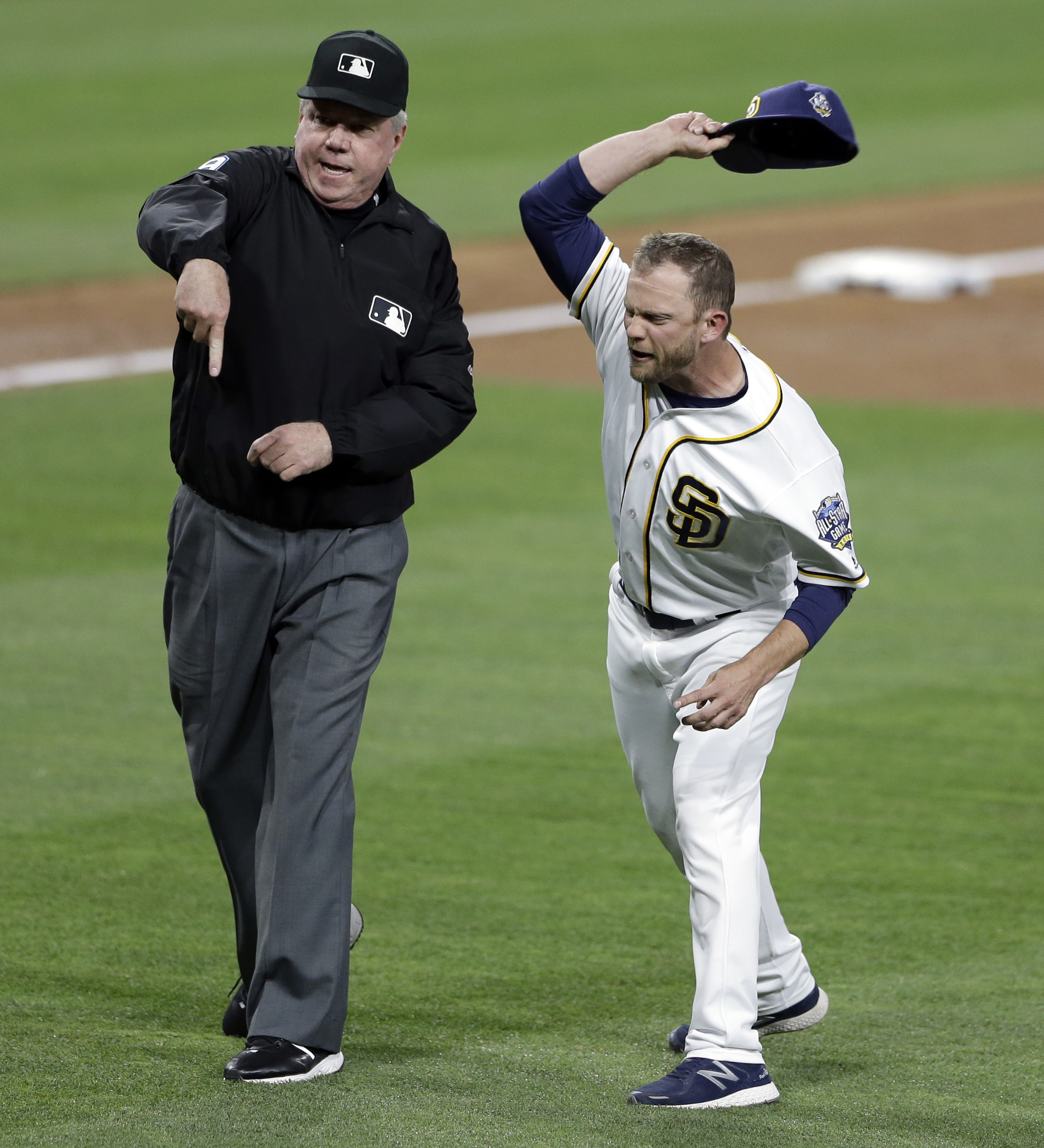 San Diego Padres manager Andy Green, right, throws his cap as he is ejected by third base umpire Brian Gorman after complaining about a call during the third inning of a baseball game against the Pittsburgh Pirates on Tuesday, April 19, 2016, in San Diego