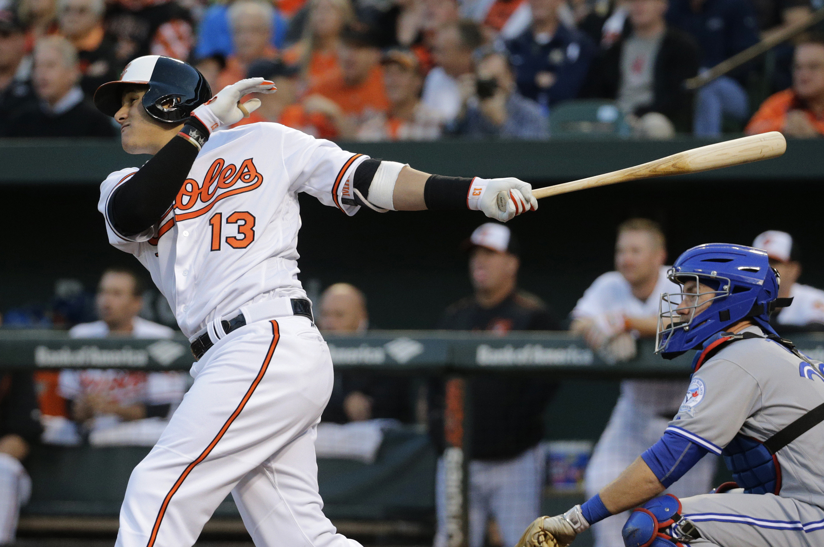 Baltimore Orioles' Manny Machado, left, doubles in front of Toronto Blue Jays catcher Josh Thole in the first inning of a baseball game in Baltimore, Wednesday, April 20, 2016. Joey Rickard scored on the play. (AP Photo/Patrick Semansky)