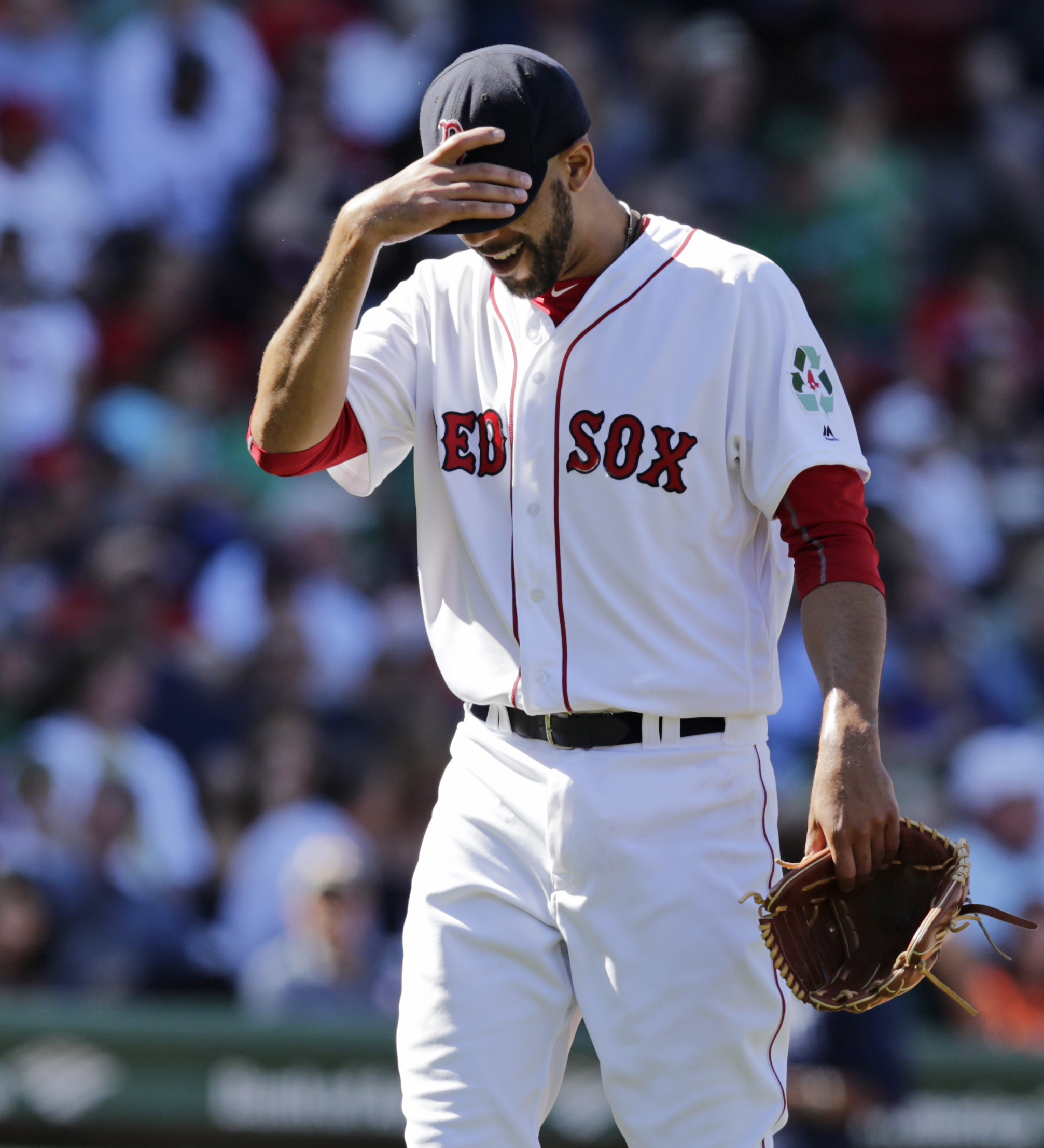 Boston Red Sox starting pitcher David Price tugs down on the brim of his cap while walking to the dugout after being pulled during the fourth inning of an MLB baseball game against the Tampa Bay Rays in Boston, Thursday, April 21, 2016. Price gave up six