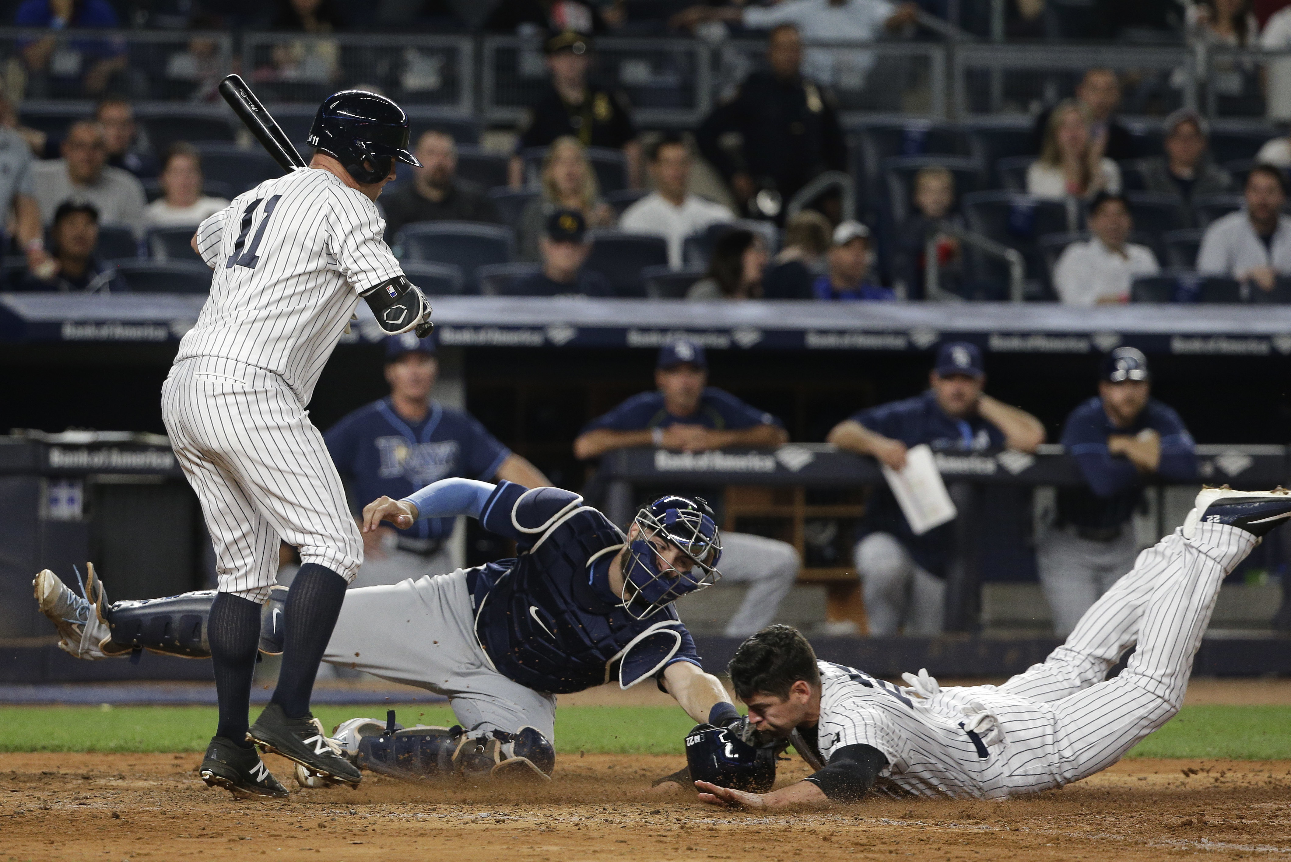 New York Yankees' Jacoby Ellsbury slides under the tag from Tampa Bay Rays catcher Curt Casali (19) to steal home as Yankees' Brett Gardner (11) steps out of the way during the fifth inning of a baseball game, Friday, April 22, 2016, in New York. (AP Phot