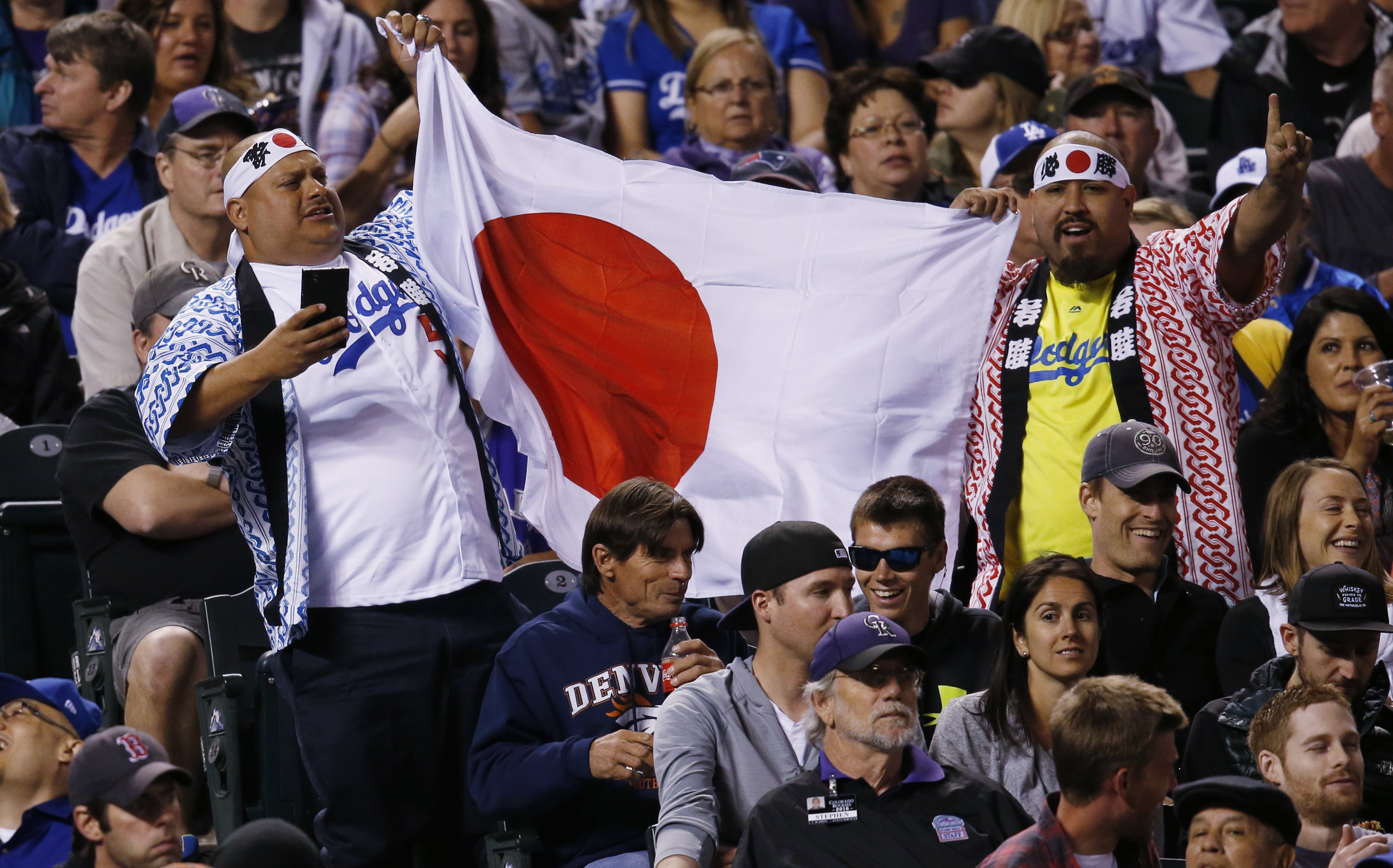 Los Angeles Dodgers fans hold up a Japanese flag after Dodgers starting pitcher Kenta Maeda, of Japan, retired Colorado Rockies' Nolan Arenado to end the sixth inning of a baseball game Saturday, April 23, 2016, in Denver. The Dodgers won 4-1. (AP Photo/D