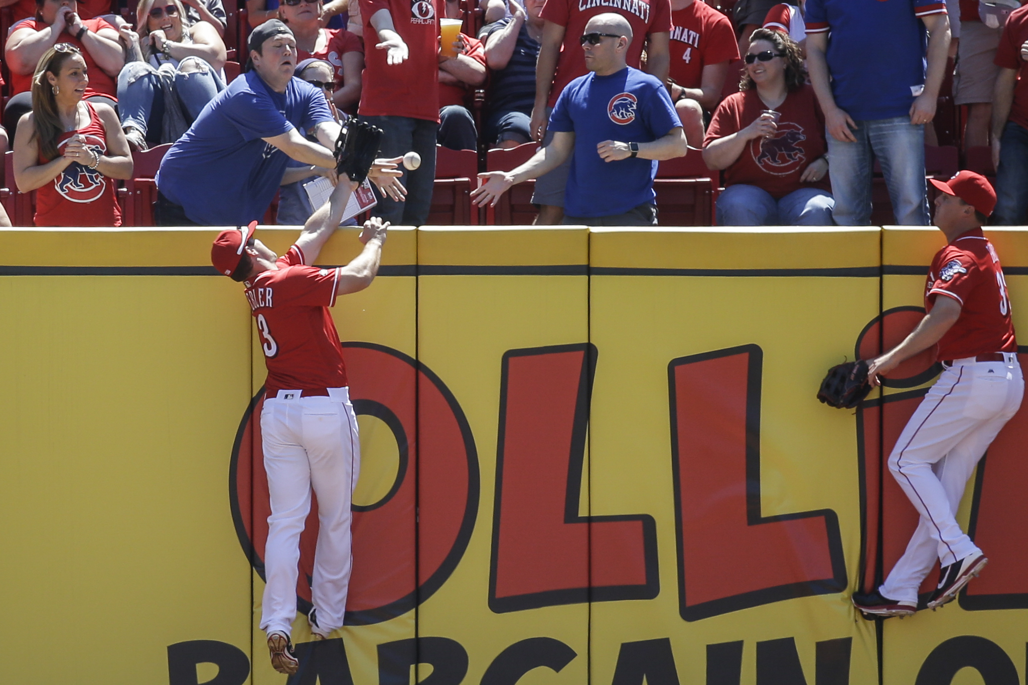 Cincinnati Reds center fielder Scott Schebler,  left, reaches for but cannot catch a two-run home run by Chicago Cubs' Anthony Rizzo as right fielder Jay Bruce, right, looks on in the first inning of a baseball game, Sunday, April 24, 2016, in Cincinnati.