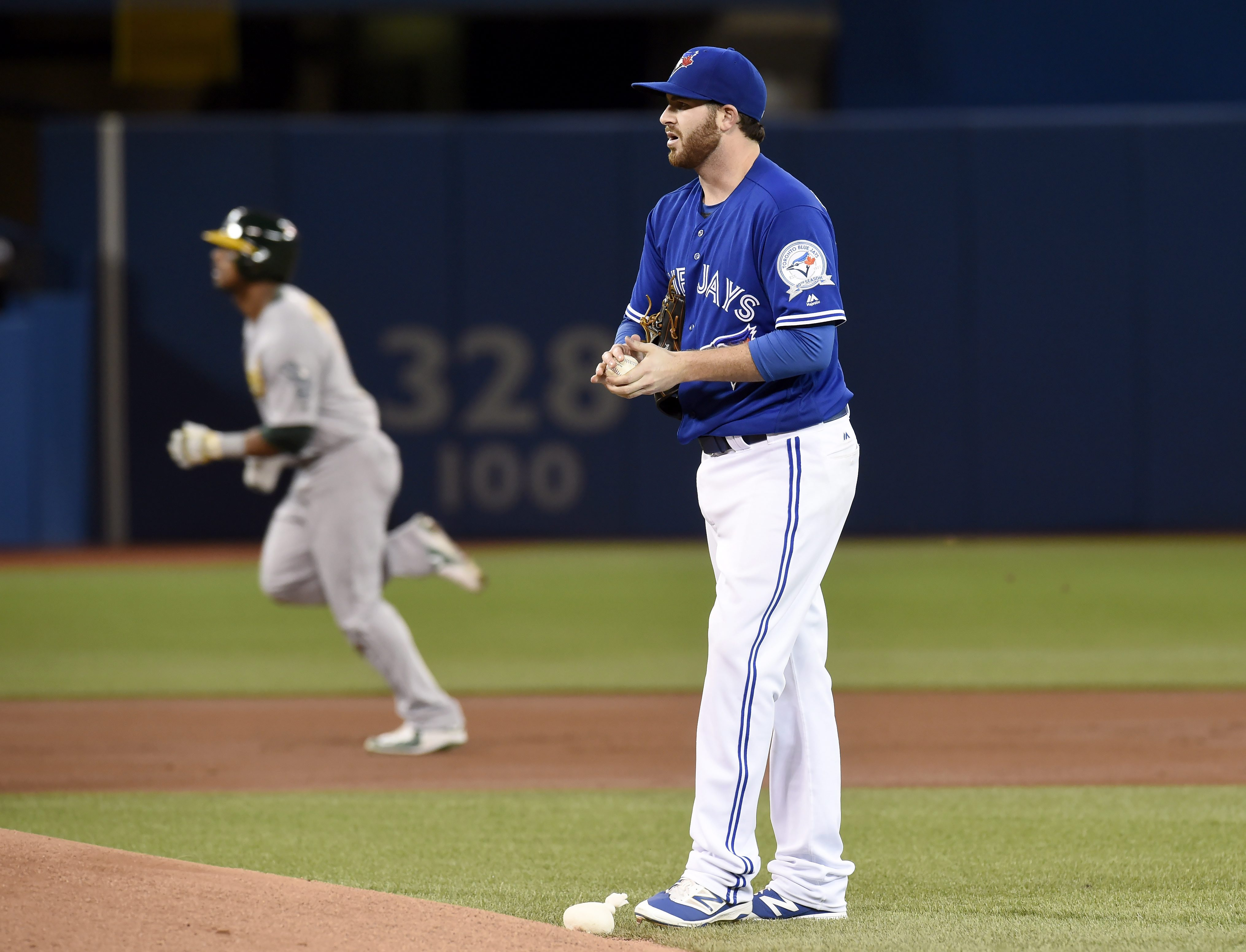 Toronto Blue Jays' Drew Hutchison, foreground, steps back as Oakland Athletics' Khris Davis runs the bases after hitting a home run during the second inning of a baseball game in Toronto, Sunday, April 24, 2016. (Frank Gunn/The Canadian Press via AP) MAND