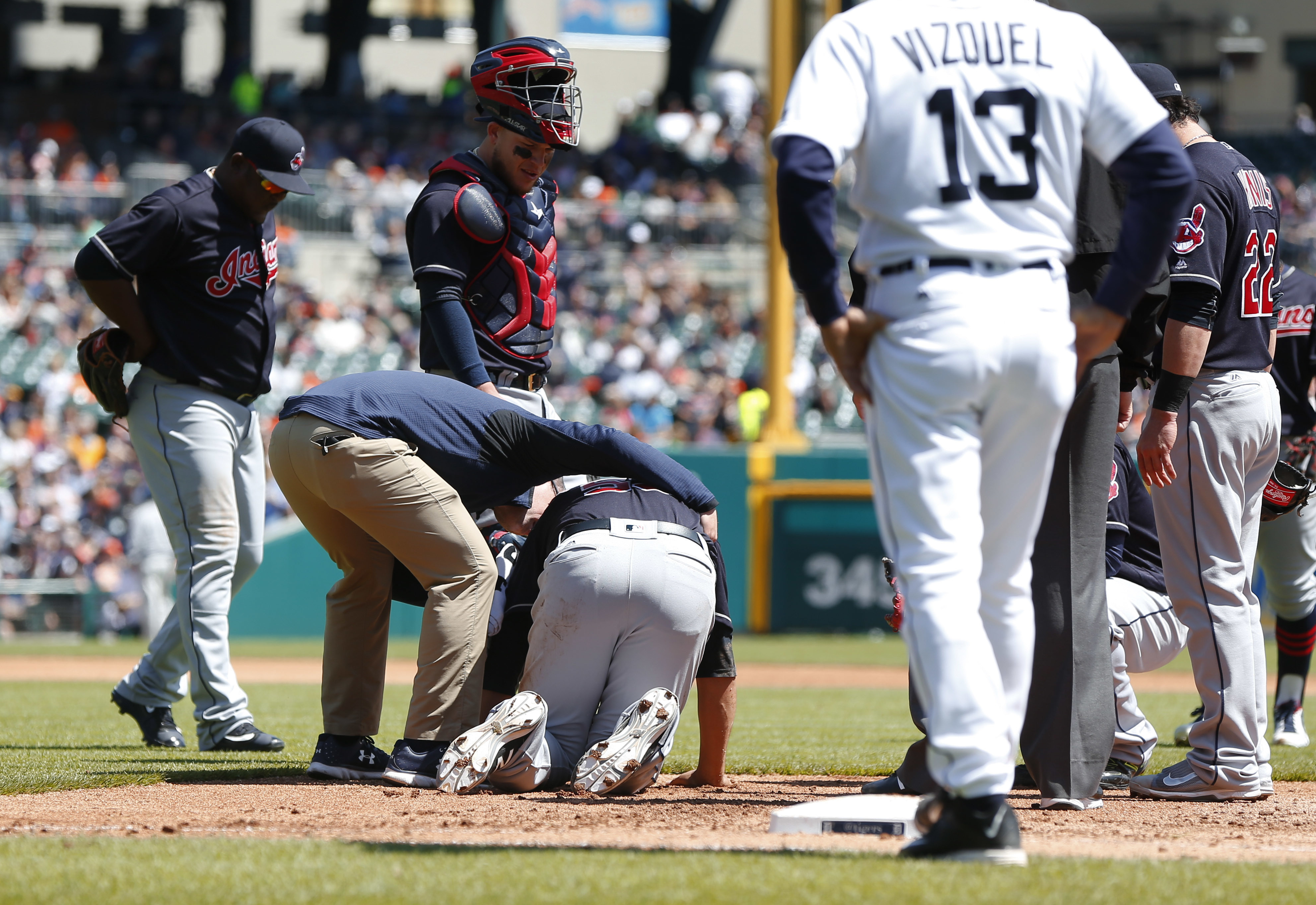 Cleveland Indians pitcher Carlos Carrasco, center, is helped by a trainer on the field in the third inning of a baseball game against the Detroit Tigers, Sunday, April 24, 2016, in Detroit. (AP Photo/Paul Sancya)