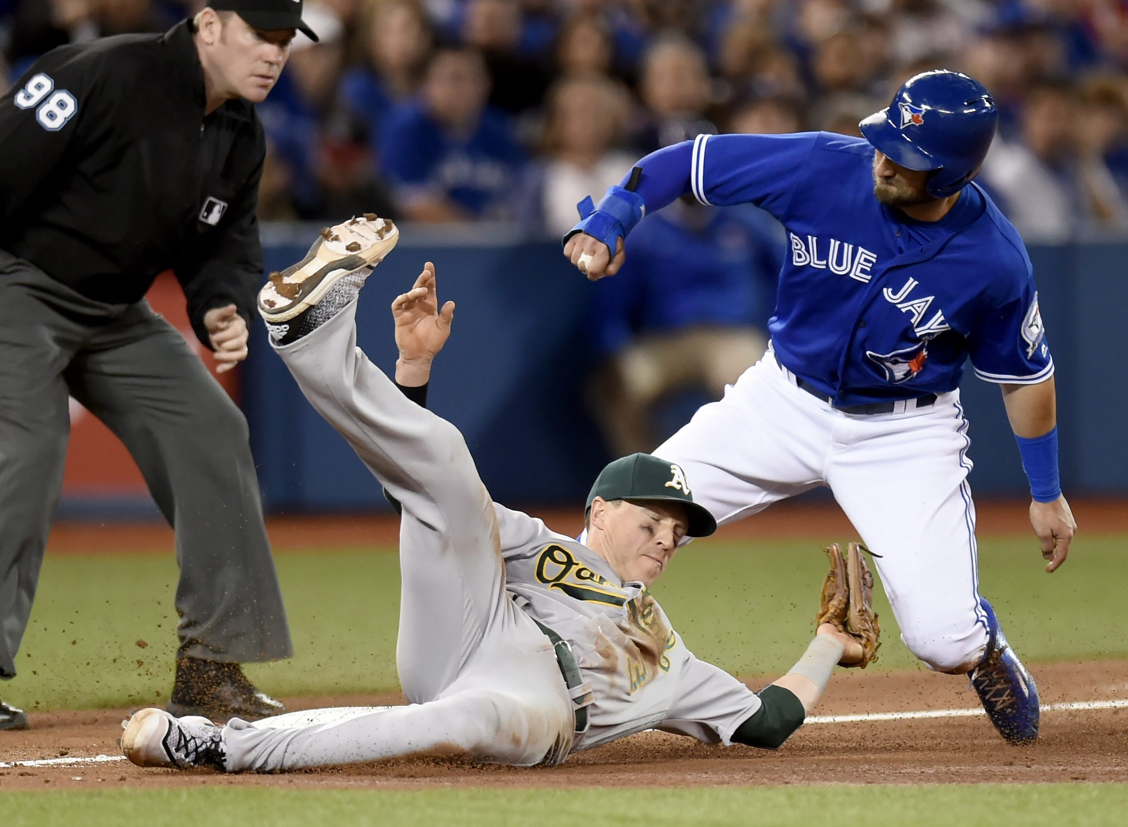 Toronto Blue Jays' Kevin Pillar, right, beats the tag from Oakland Athletics' Chris Coghlan to steal third base during the fifth inning of a baseball game in Toronto, Sunday, April 24, 2016. (Frank Gunn/The Canadian Press via AP) MANDATORY CREDIT