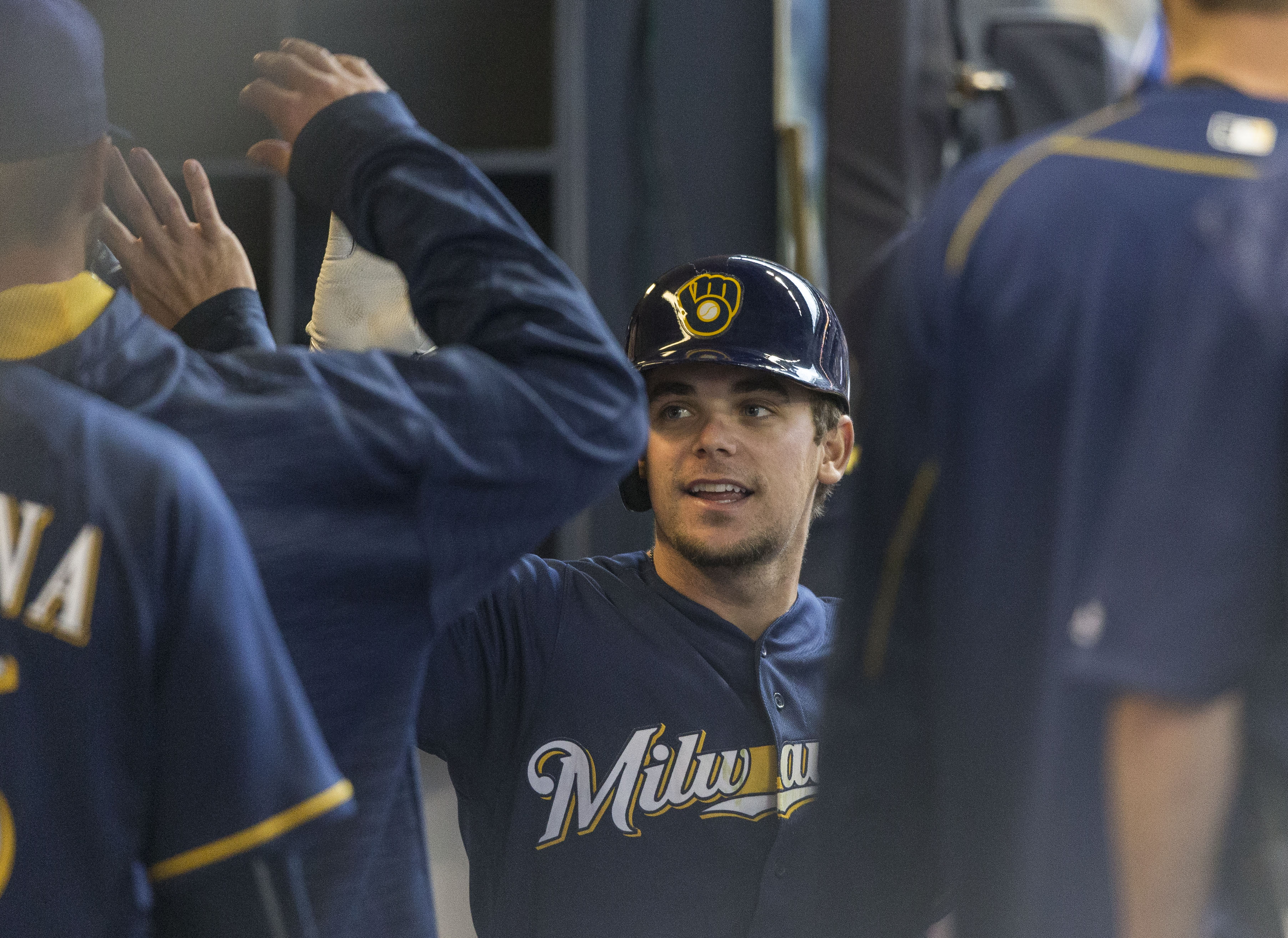 Milwaukee Brewers' Scooter Gennett gets a high-fives from teammates in the dugout after hitting a solo home run off Philadelphia Phillies' Jerad Eickhoff during the sixth inning of a baseball game Sunday, April 24, 2016, in Milwaukee. (AP Photo/Tom Lynn)