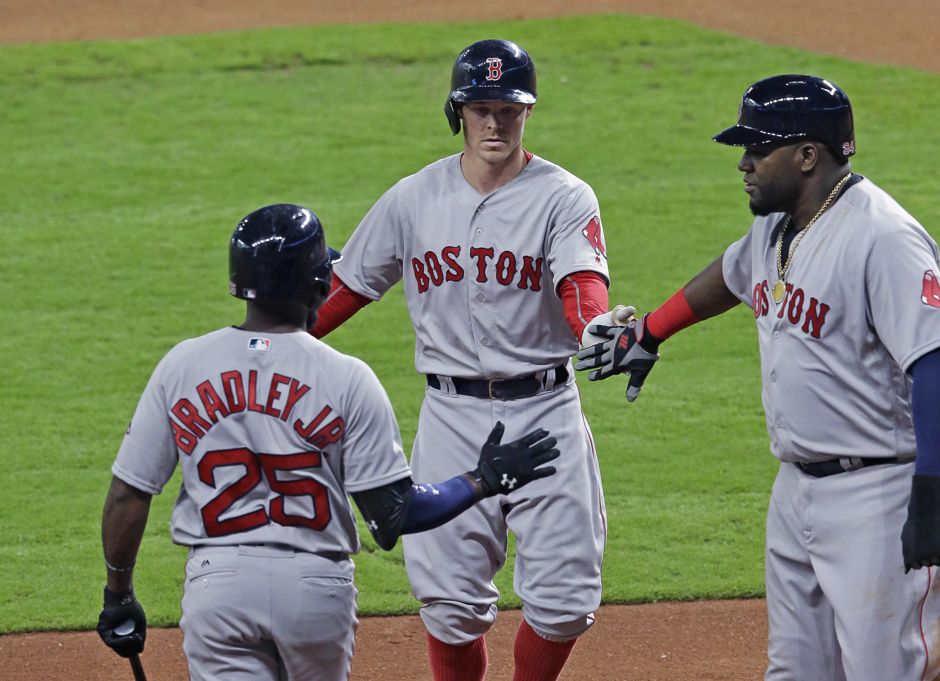 Boston Red Sox Jackie Bradley Jr. (25) and David Ortiz, right, congratulate Brock Holt, center, on a sacrifice fly to bring in Ortiz with the bases loaded against the Houston Astros in the first inning of a baseball game, Sunday, April 24, 2016, in Housto