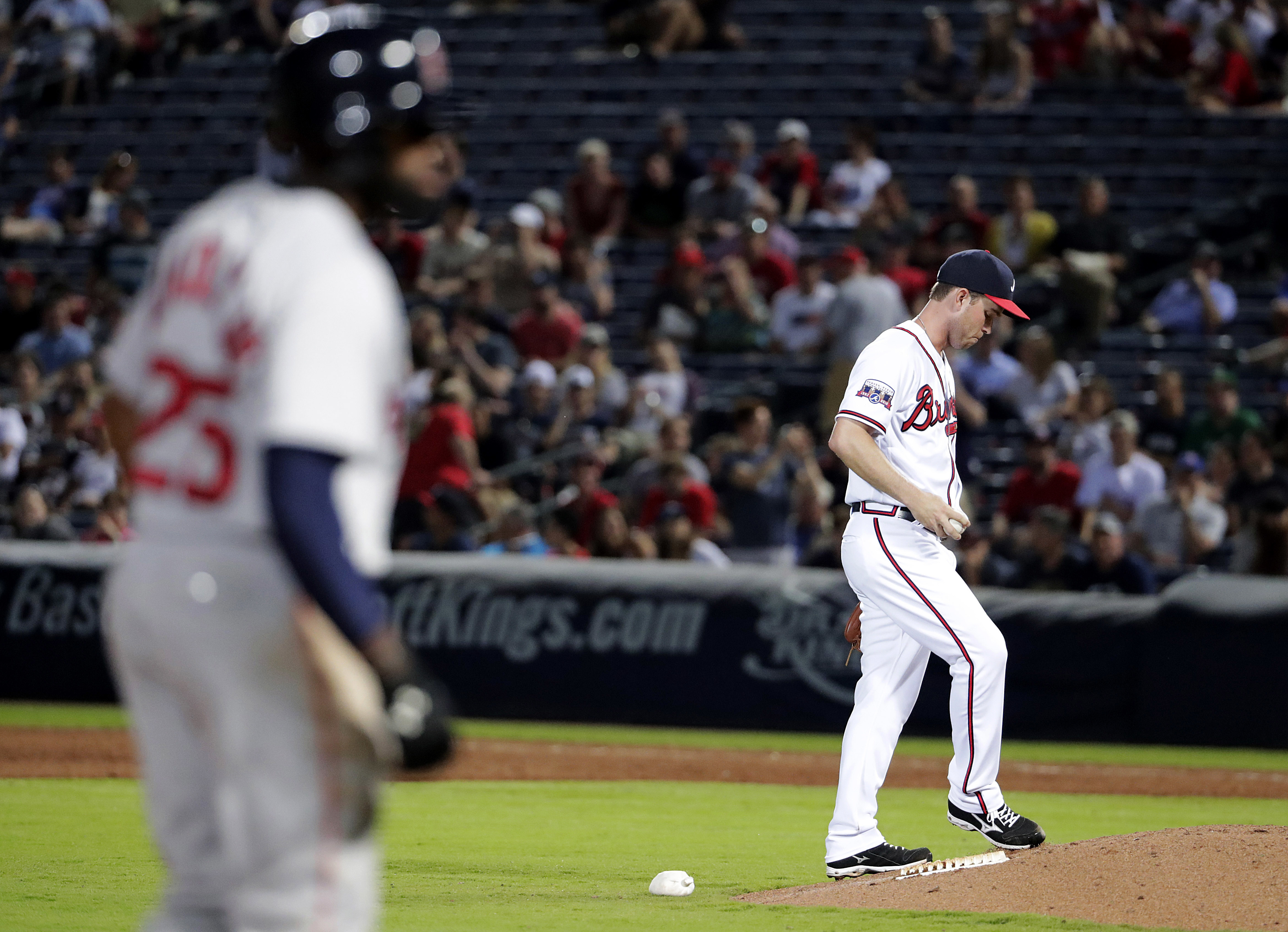Atlanta Braves relief pitcher Ryan Weber, right, kicks the dirt after giving up a triple to Boston Red Sox's Jackie Bradley Jr., left, for a run in the ninth inning of a baseball game Tuesday, April 26, 2016, in Atlanta. Weber allowed fun runs in the nint