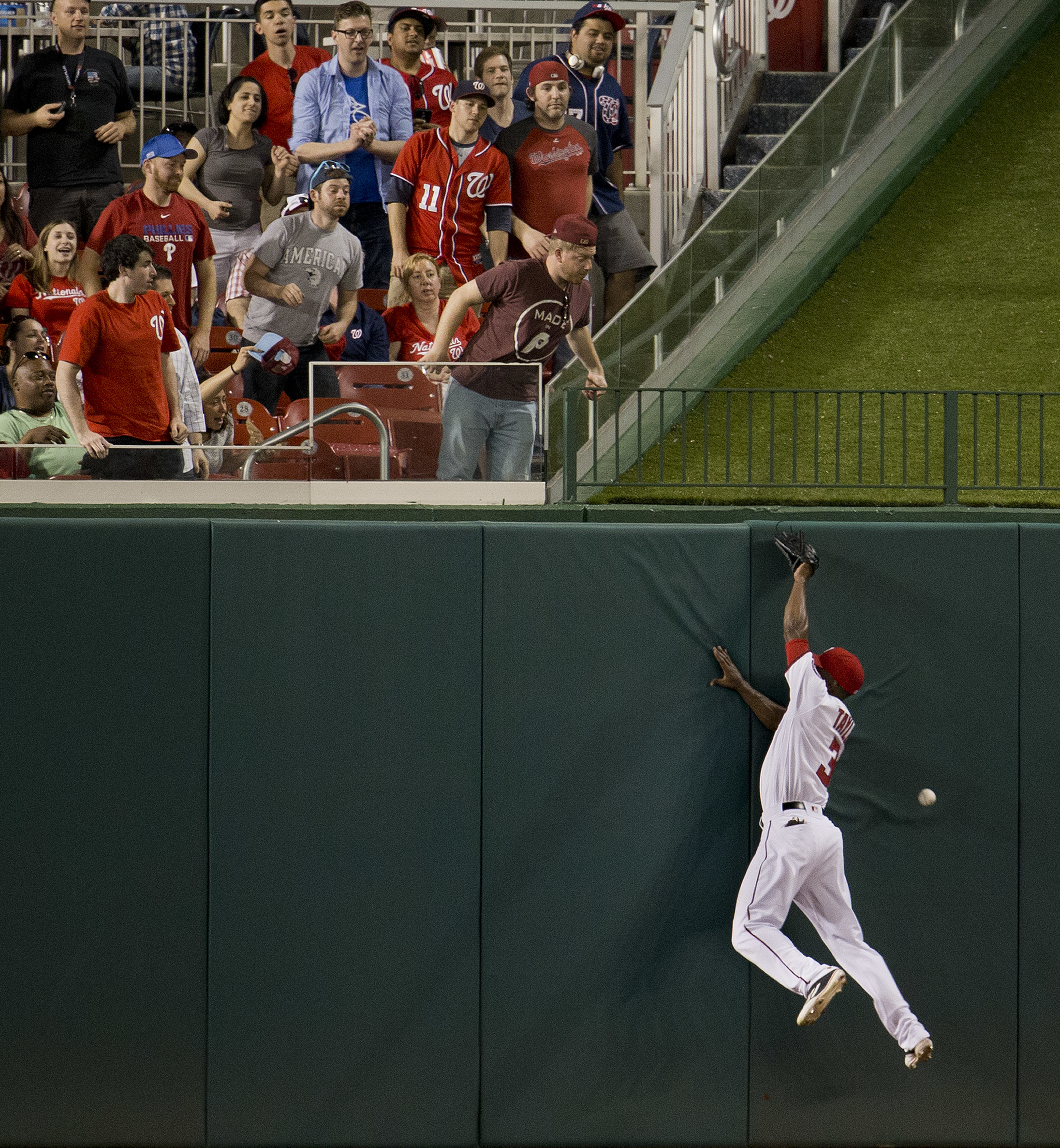 Fans in centerfield watch as Washington Nationals Michael Taylor tries to catch a ball hit by Philadelphia Phillies Maikel Franco for a double scoring Phillies Andres Blanco for the go-ahead run in the seventh inning of a baseball game, Tuesday, April 26,