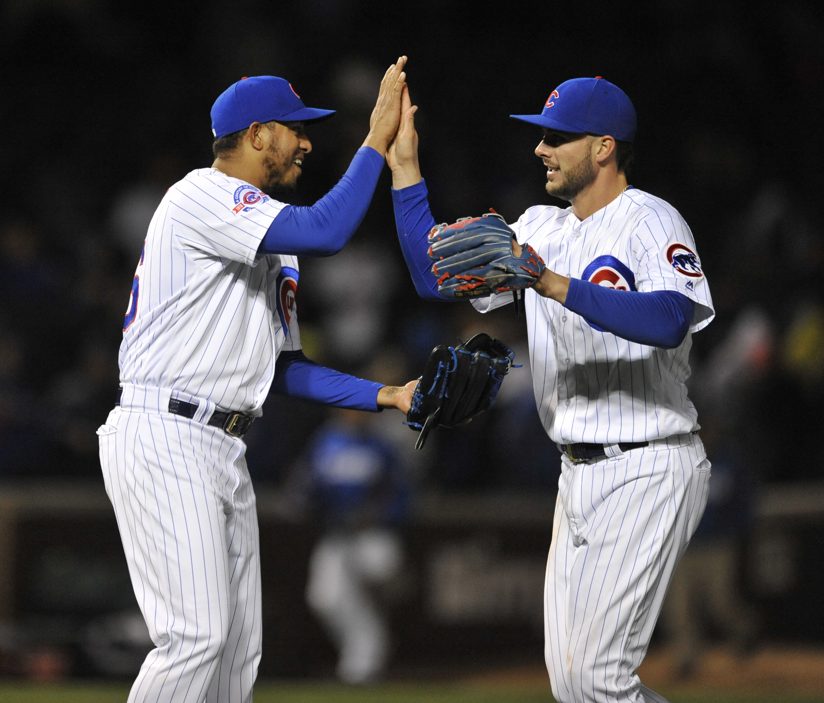 Chicago Cubs closing pitcher Hector Rodon left, celebrates with Kris Bryant right, after the Cubs defeated the Milwaukee Brewers 4-3 in a baseball game Tuesday, April 26, 2016, in Chicago. (AP Photo/Paul Beaty)