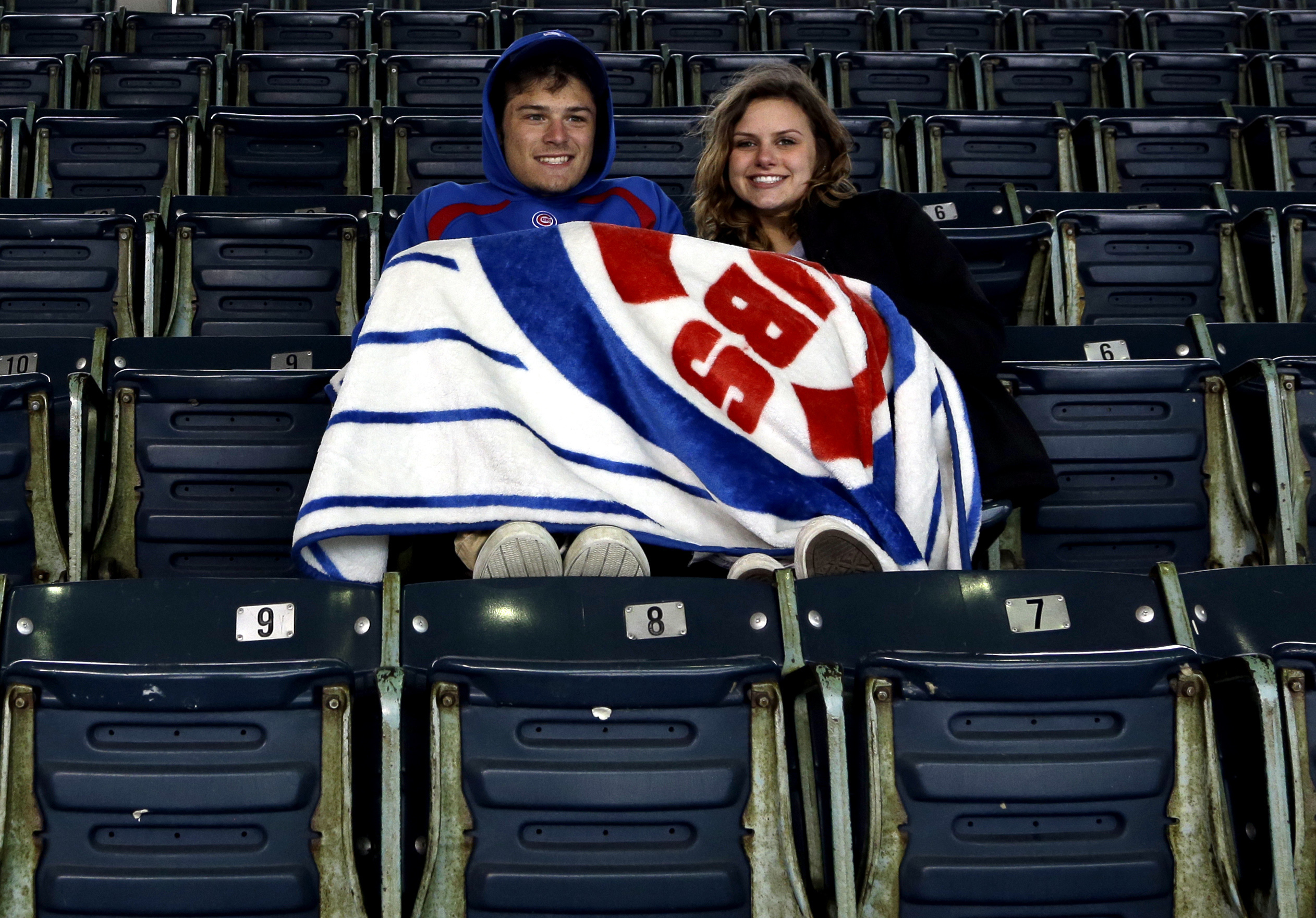 Nick Arthur, left, Nicole Weber sit as they wait for a baseball game between the Milwaukee Brewers and the Chicago Cubs on Wednesday, April 27, 2016, in Chicago. (AP Photo/Nam Y. Huh)