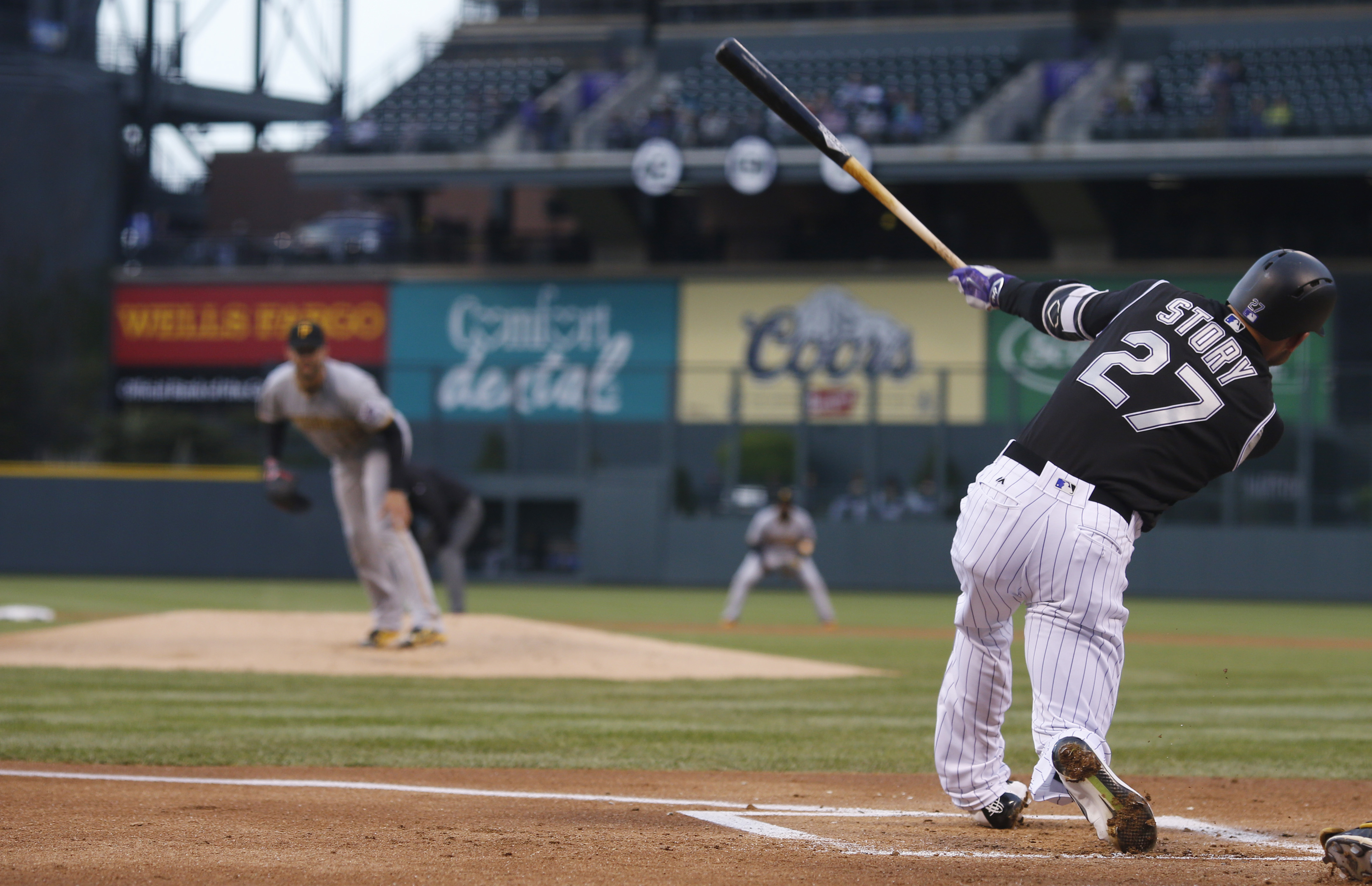 Colorado Rockies' Trevor Story, front, strikes out on a pitch from Pittsburgh Pirates' Jonathon Niese during the first inning of a baseball game Wednesday, April 27, 2016, in Denver. (AP Photo/David Zalubowski)