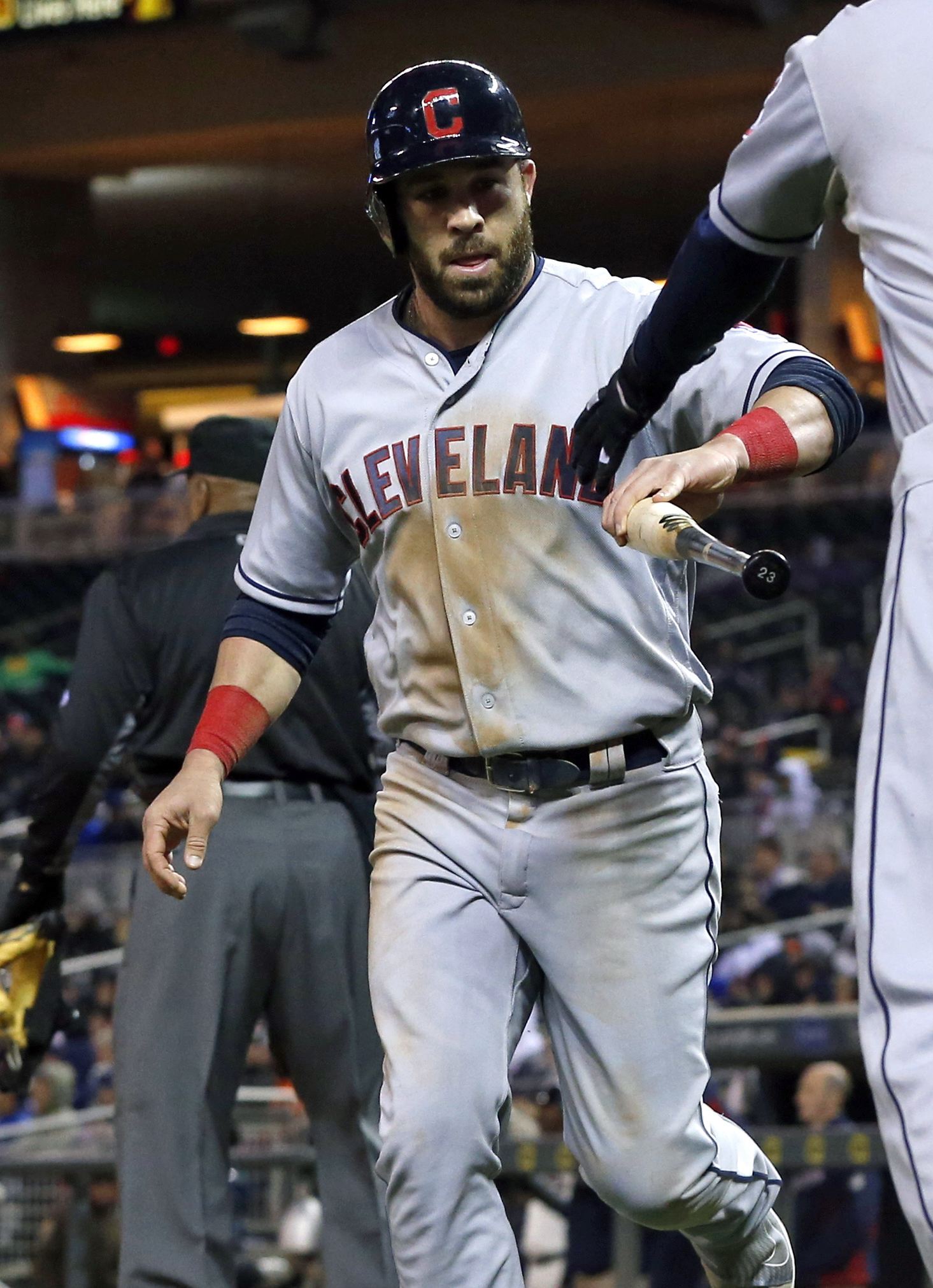 Cleveland Indians' Jason Kipnis hands a bat to a bat boy after he scored on a single by Michael Brantley in the fifth inning of a baseball game Wednesday, April 27, 2016, in Minneapolis. (AP Photo/Jim Mone)