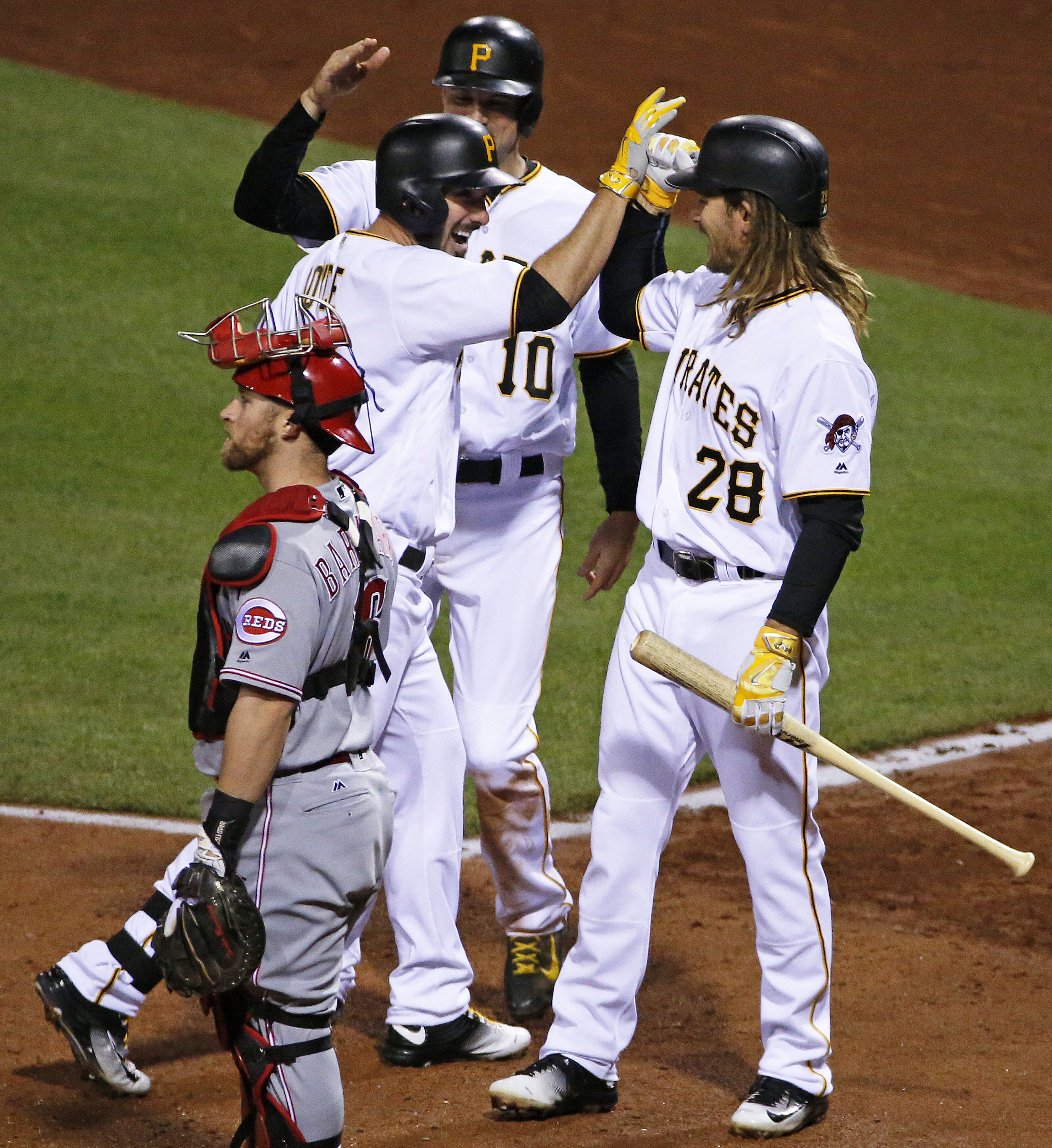 Pittsburgh Pirates' Matt Joyce, center, celebrates his two-run home run off Cincinnati Reds relief pitcher J.J. Hoover with teammates Jordy Mercer, rear, and John Jaso (28), next to Cincinnati Reds catcher Tucker Barnhart during the seventh inning of a ba
