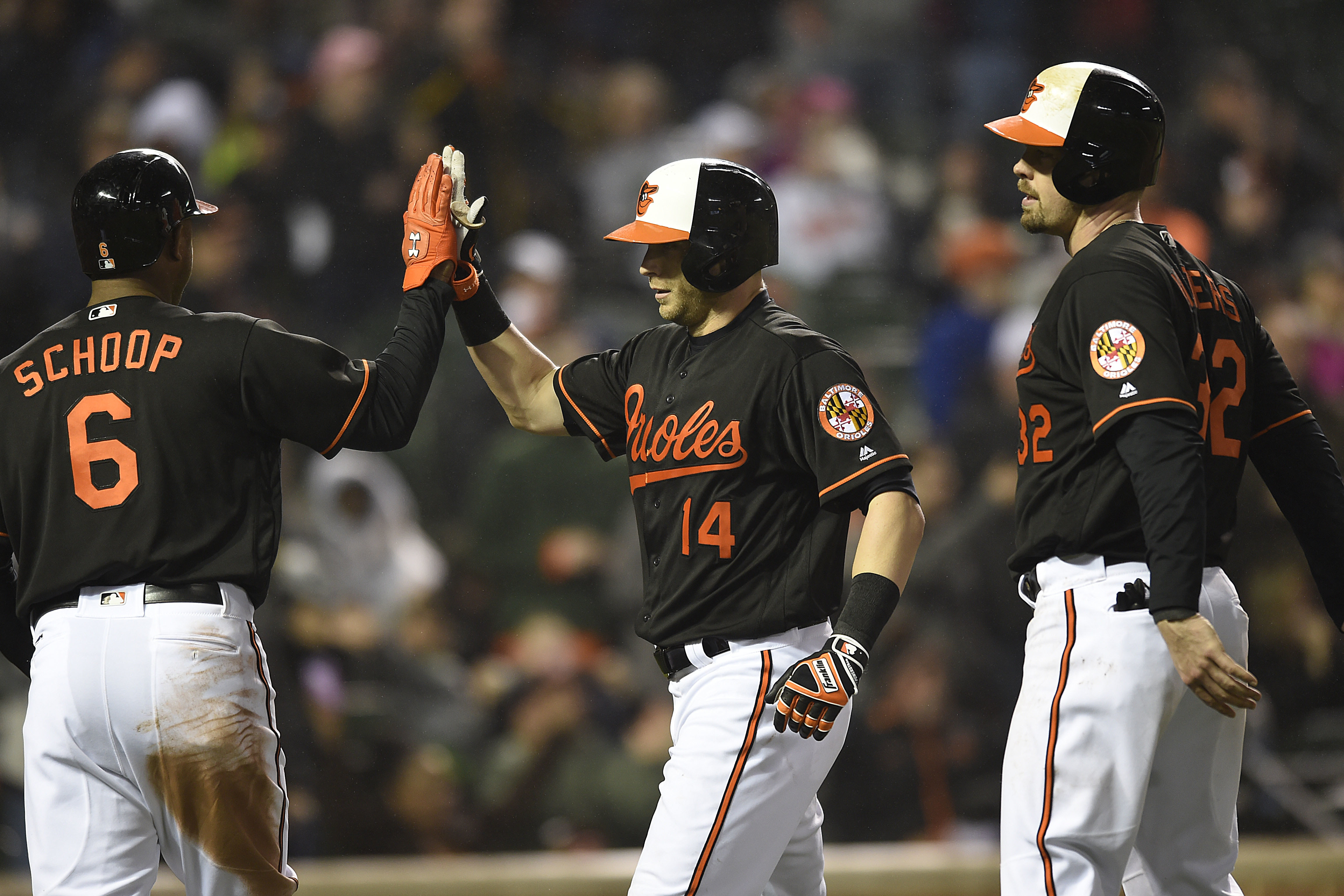 Baltimore Orioles Nolan Reimold, center, is congratulated by Jonathan Schoop, left, and Matt Wieters after hitting a three-run home run against the Chicago White Sox during the seventh inning of a baseball game, Friday, April 29, 2016, in Baltimore. The O