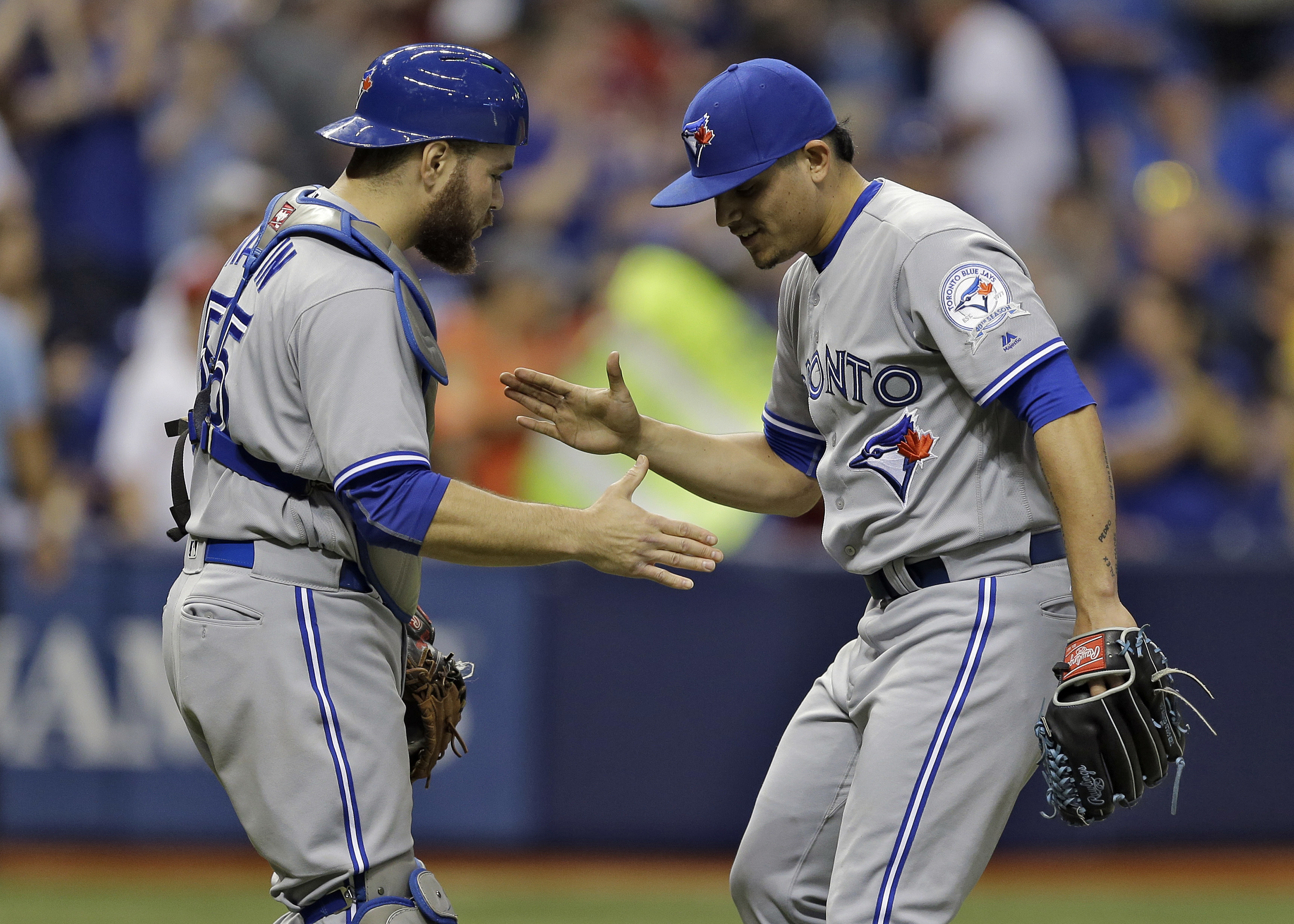 Toronto Blue Jays relief pitcher Roberto Osuna, right, celebrates with catcher Russell Martin after they defeated the Tampa Bay Rays in a baseball game Friday, April 29, 2016, in St. Petersburg, Fla. (AP Photo/Chris O'Meara)