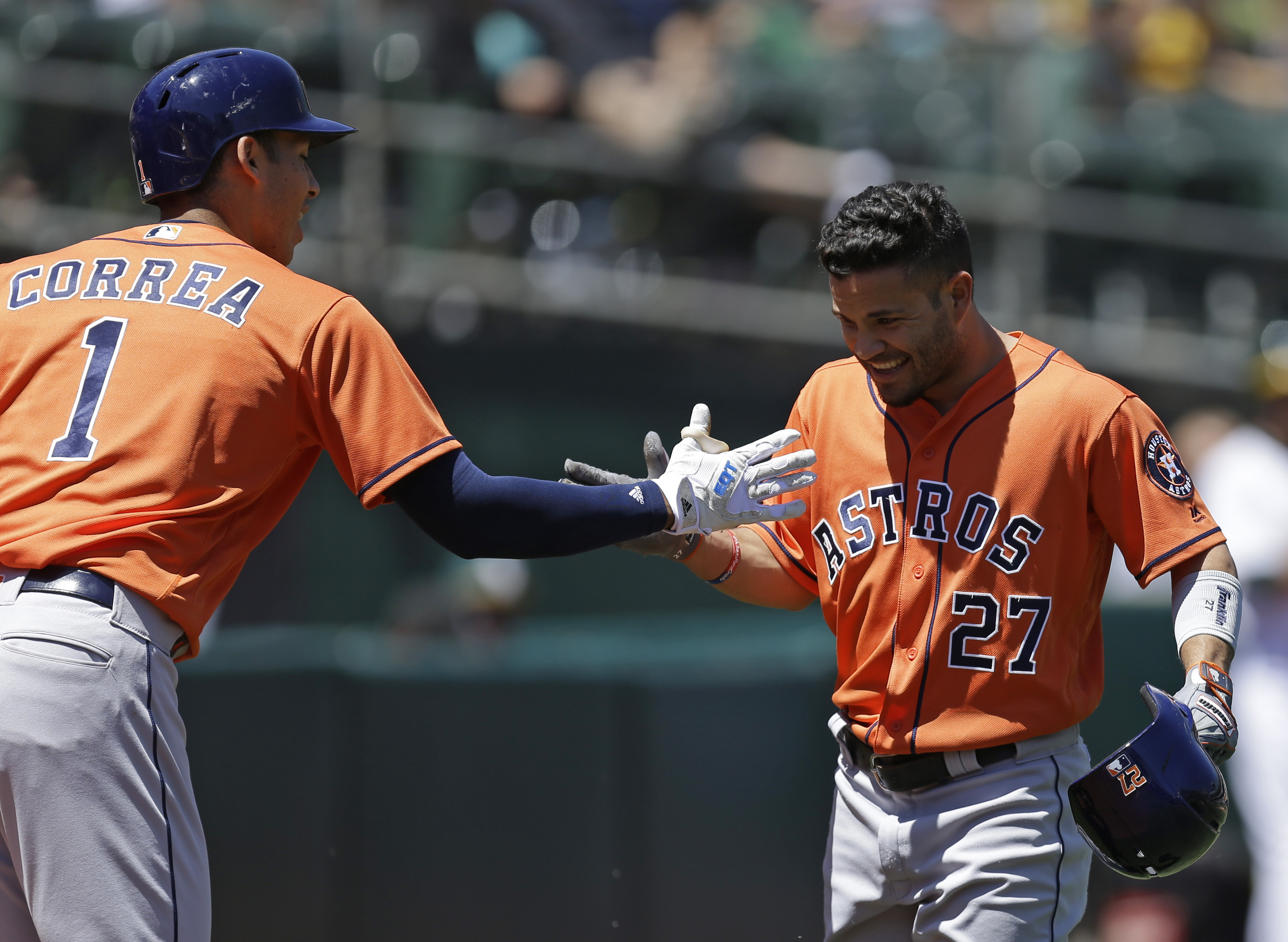 Houston Astros' Jose Altuve, right, celebrates with Carlos Correa (1) after hitting a home run off Oakland Athletics' Rich Hill in the first inning of a baseball game, Sunday, May 1, 2016, in Oakland, Calif. (AP Photo/Ben Margot)