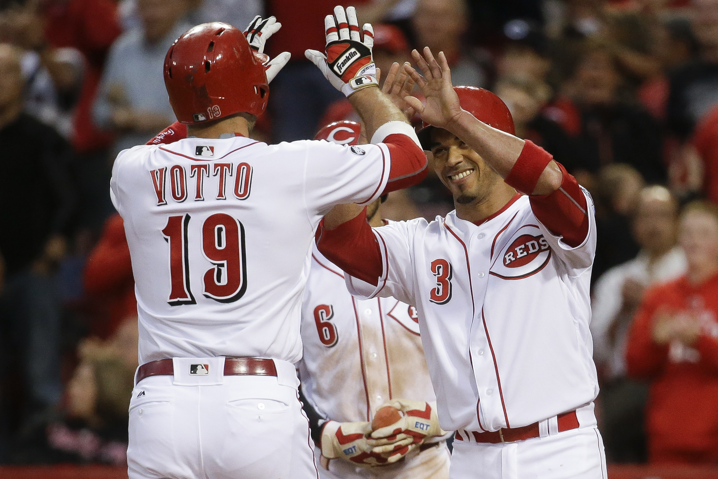 Cincinnati Reds' Joey Votto (19) celebrates hitting a three-run home run off San Francisco Giants starting pitcher Johnny Cueto (47) with Ivan De Jesus (3) and Billy Hamilton (6) in the third inning of a baseball game, Monday, May 2, 2016, in Cincinnati.