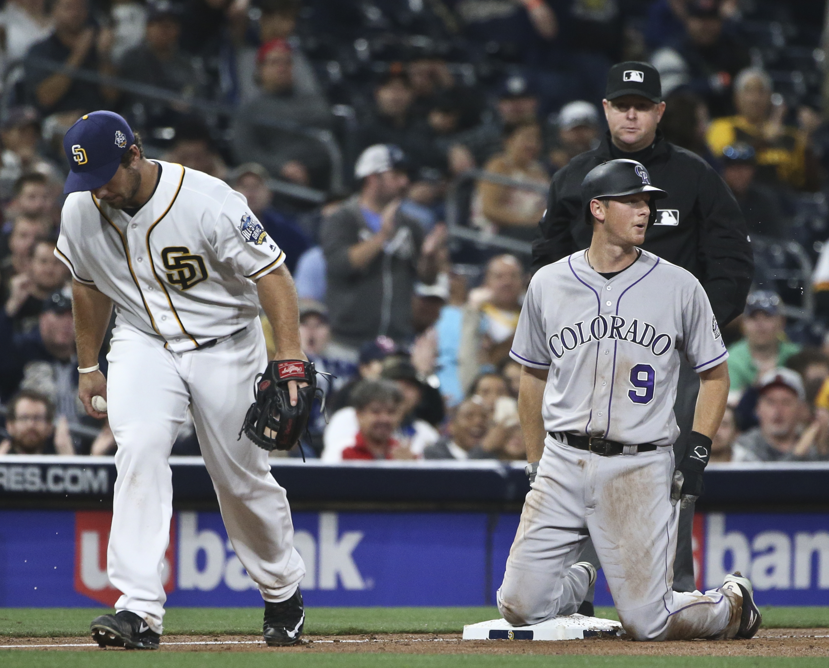 Colorado Rockies' DJ LeMahieu kneels at third base after being caught stealing with two out against the San Diego Padres in the fifth inning of a baseball game Monday, May 2, 2016, in San Diego. (AP Photo/Lenny Ignelzi)