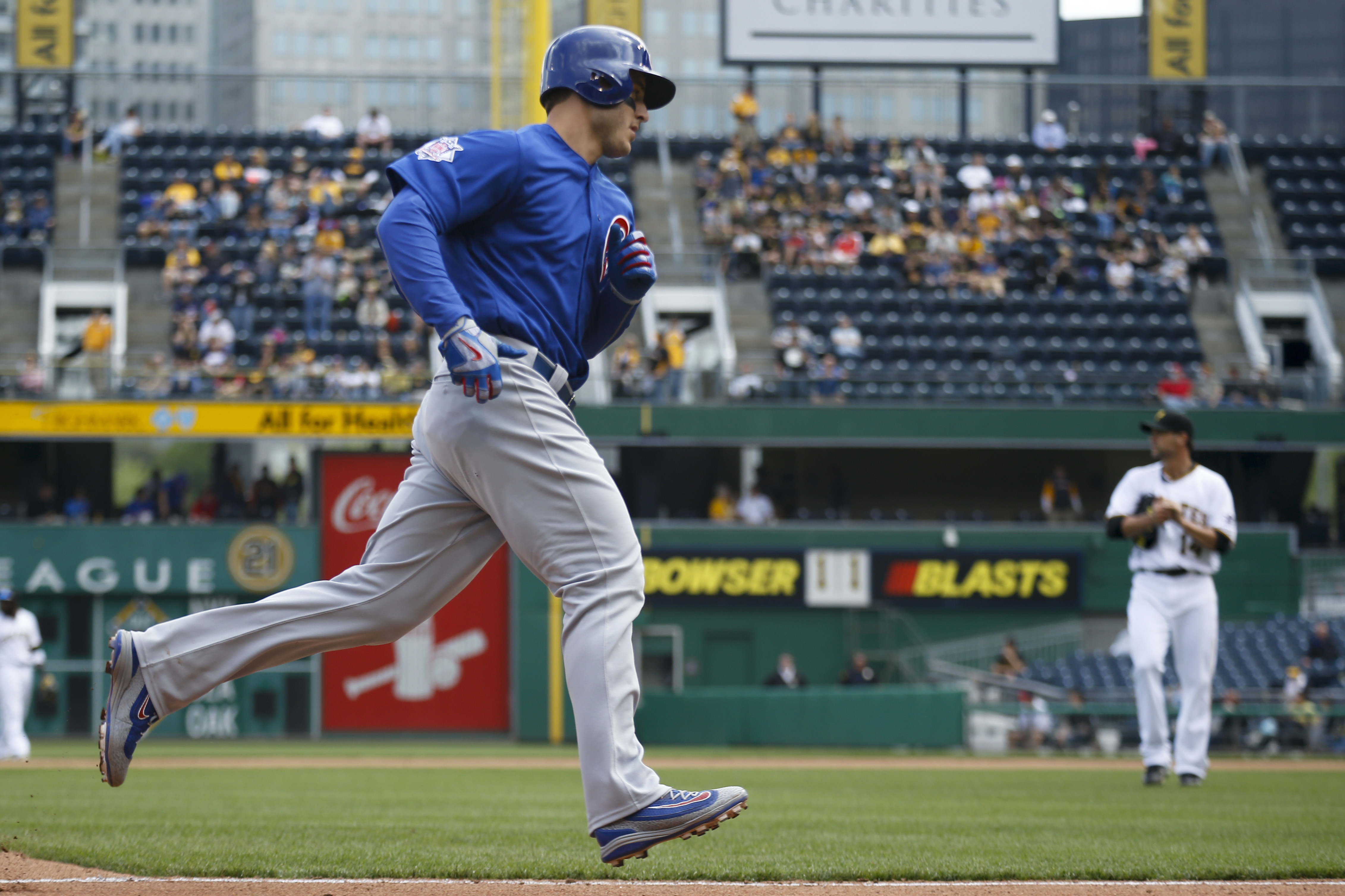 Chicago Cubs' Anthony Rizzo, left, rounds third in front of Pittsburgh Pirates relief pitcher Ryan Vogelsong after hitting a solo home run off him in the seventh inning of a baseball game, Wednesday, May 4, 2016, in Pittsburgh. (AP Photo/Keith Srakocic)