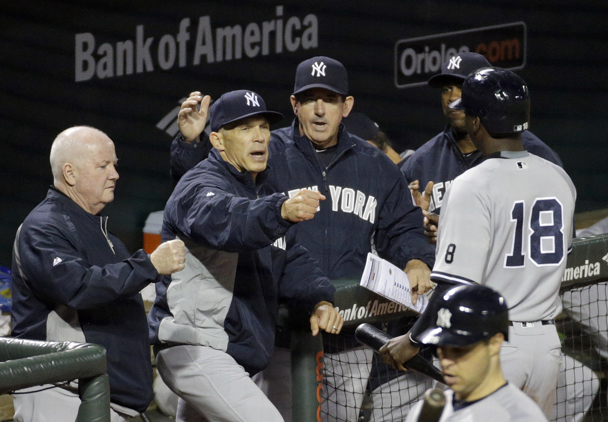 New York Yankees manager Joe Girardi, second from left, greets Didi Gregorius (18) after he scored when teammate Brett Gardner was hit by a pitch with the bases loaded in the eighth inning of a baseball game against the Baltimore Orioles in Baltimore, Wed