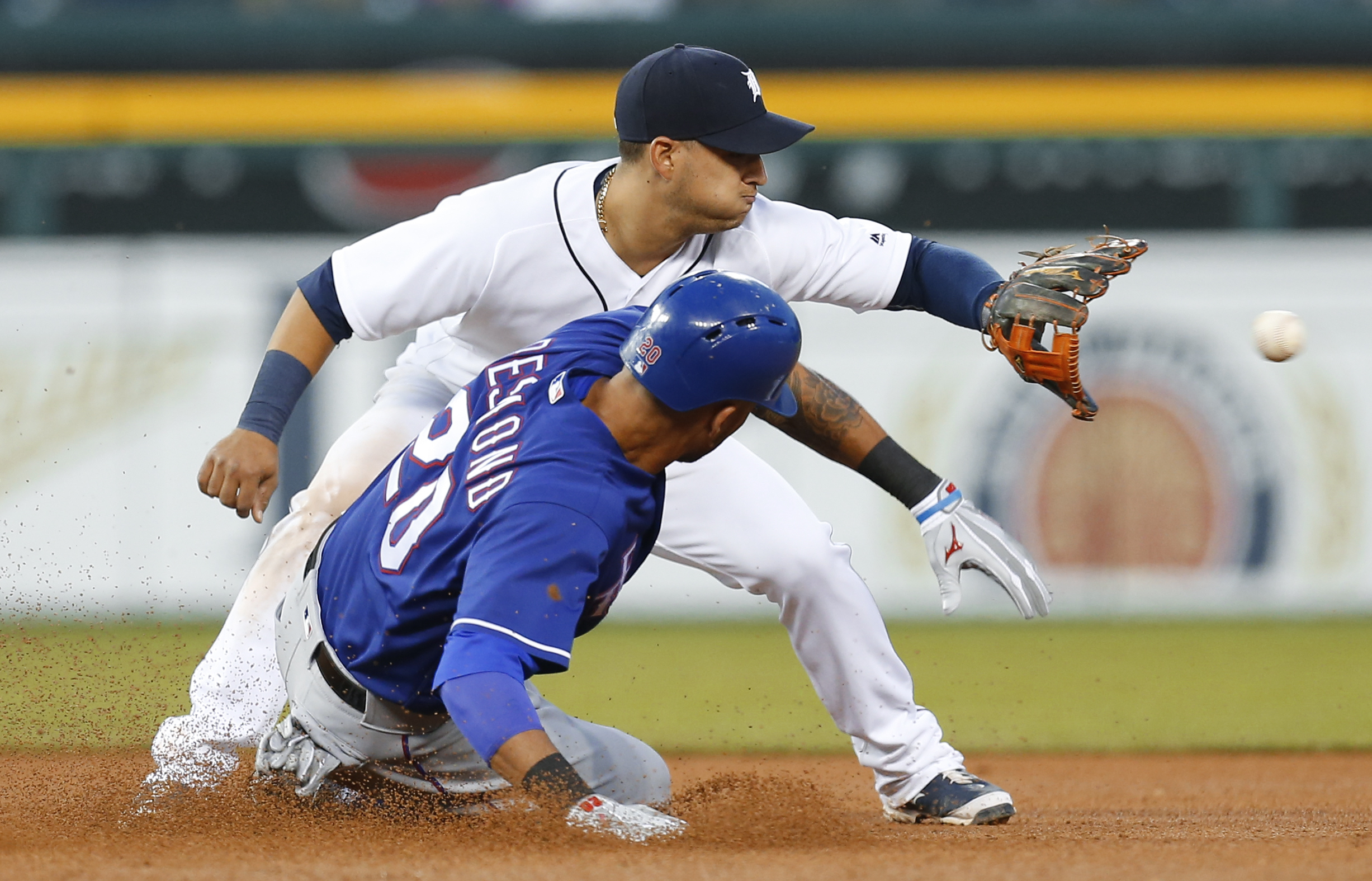 Texas Rangers' Ian Desmond (20) slides into second base safely for a double under the tag of Detroit Tigers shortstop Jose Iglesias in the sixth inning of a baseball game Friday, May 6, 2016 in Detroit. (AP Photo/Paul Sancya)