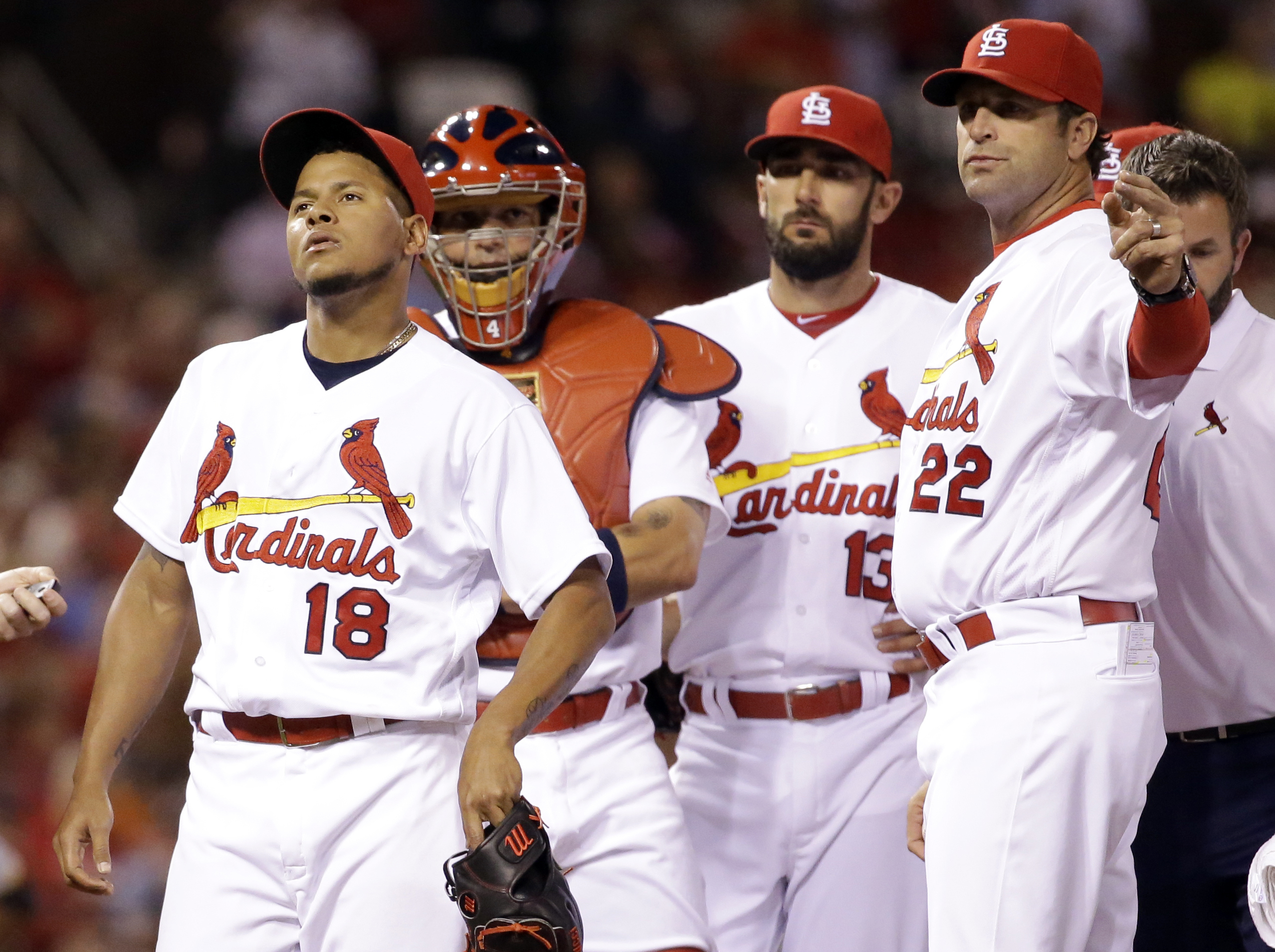 St. Louis Cardinals starting pitcher Carlos Martinez, left, leaves the game as Cardinals manager Mike Matheny, right, calls for a new pitcher while catcher Yadier Molina, second from left, and Matt Carpenter watch during the fourth inning of a baseball ga