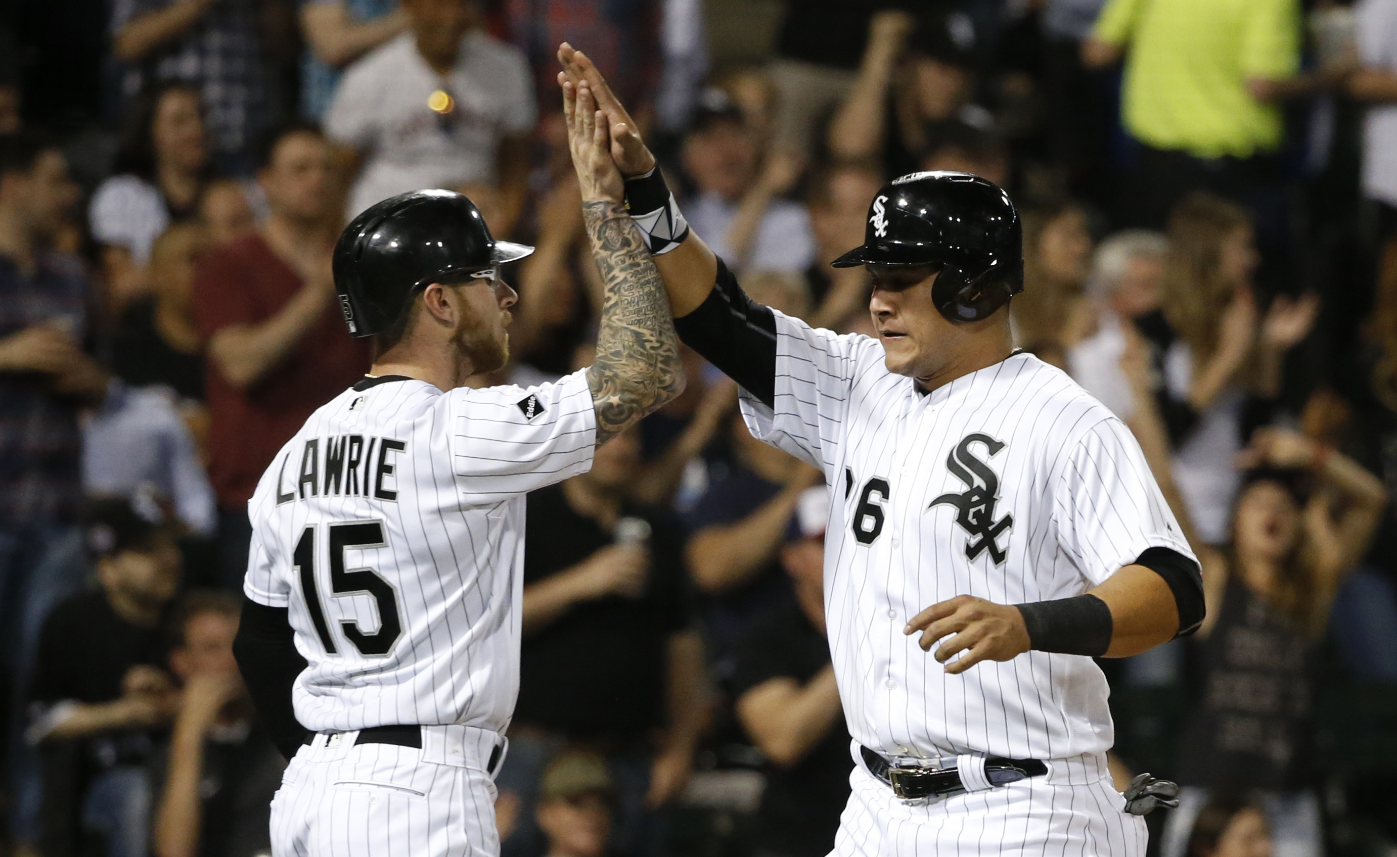 Chicago White Sox's Brett Lawrie (15) and Avisail Garcia celebrate after scoring on a single by Tyler Saladin off a pitch from Minnesota Twins relief pitcher Fernando Abad during the seventh inning of a baseball game Friday, May 6, 2016, in Chicago. (AP P