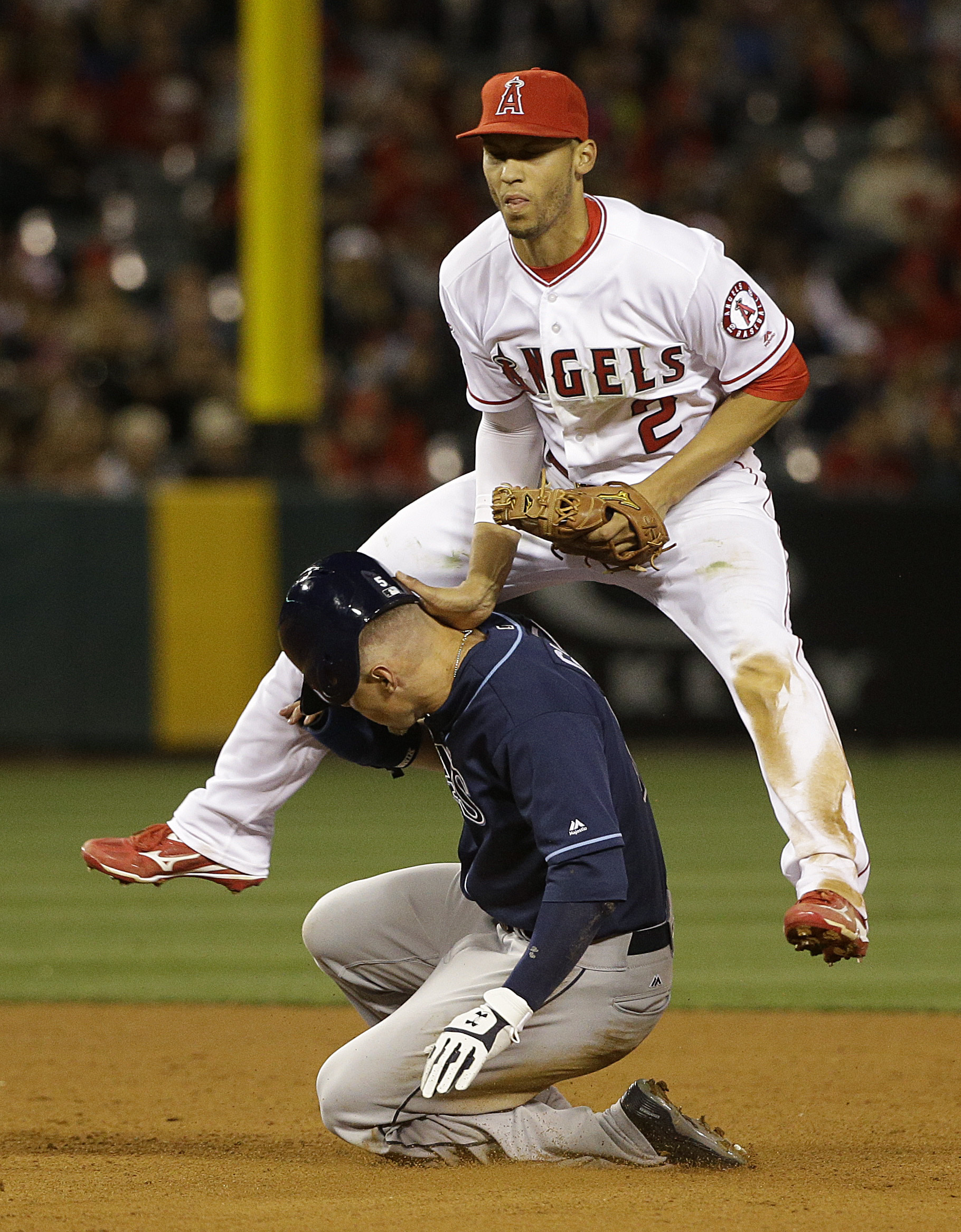 Los Angeles Angels' Andrelton Simmons, top, watches his throw to first base after forcing out Tampa Bay Rays' Brandon Guyer during the fifth inning of a baseball game, Friday, May 6, 2016, in Anaheim, Calif. (AP Photo/Jae C. Hong)