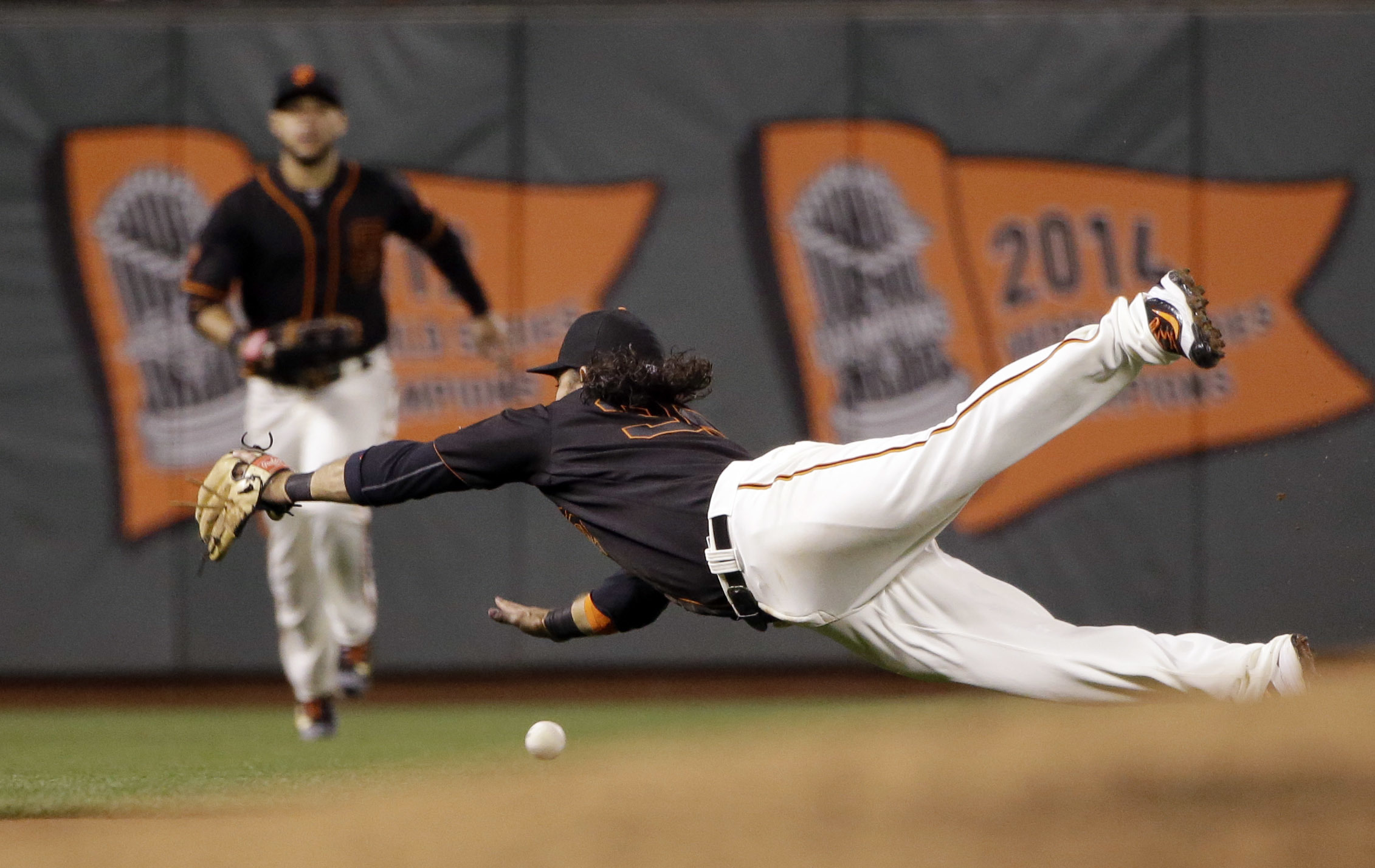 San Francisco Giants shortstop Brandon Crawford dives but can't catch a fly ball from Colorado Rockies' Mark Reynolds during the sixth inning of a baseball game Friday, May 6, 2016, in San Francisco. (AP Photo/Marcio Jose Sanchez)