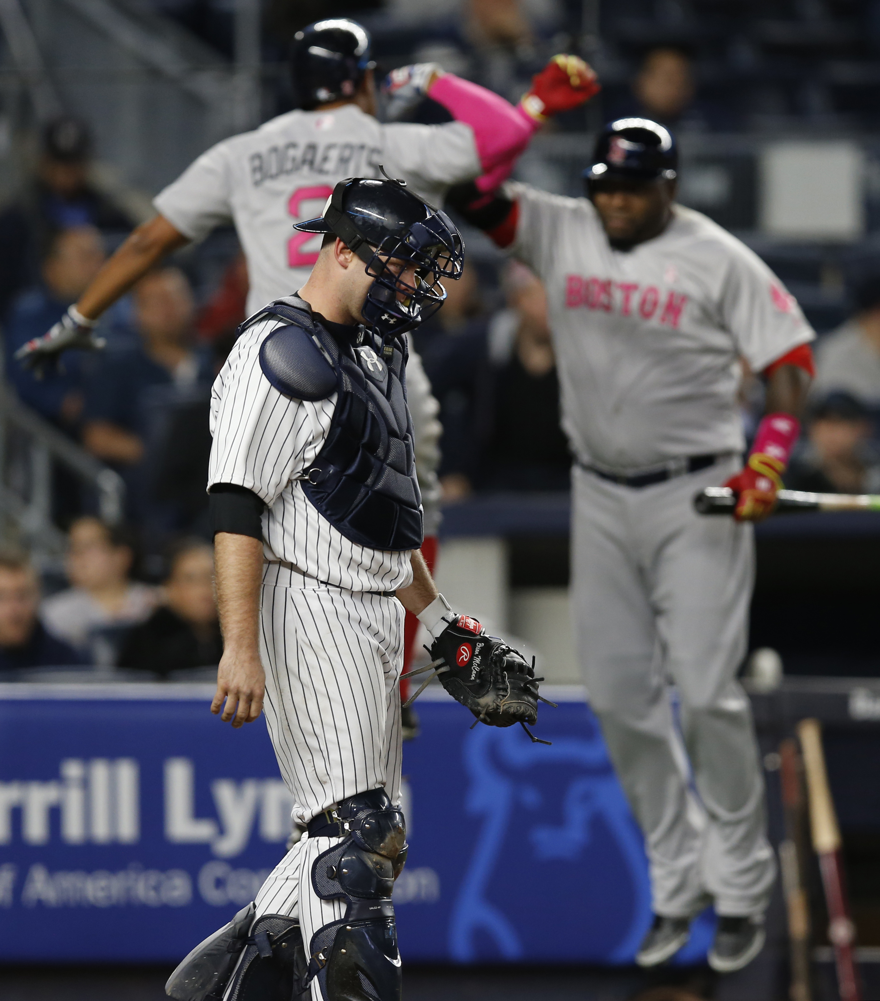 Boston Red Sox shortstop Xander Bogaerts (2) and Red Sox designated hitter David Ortiz celebrate behind New York Yankees catcher Brian McCann (34) during the seventh inning after Bogaerts hit a solo home run off New York Yankees relief pitcher Chasen Shre
