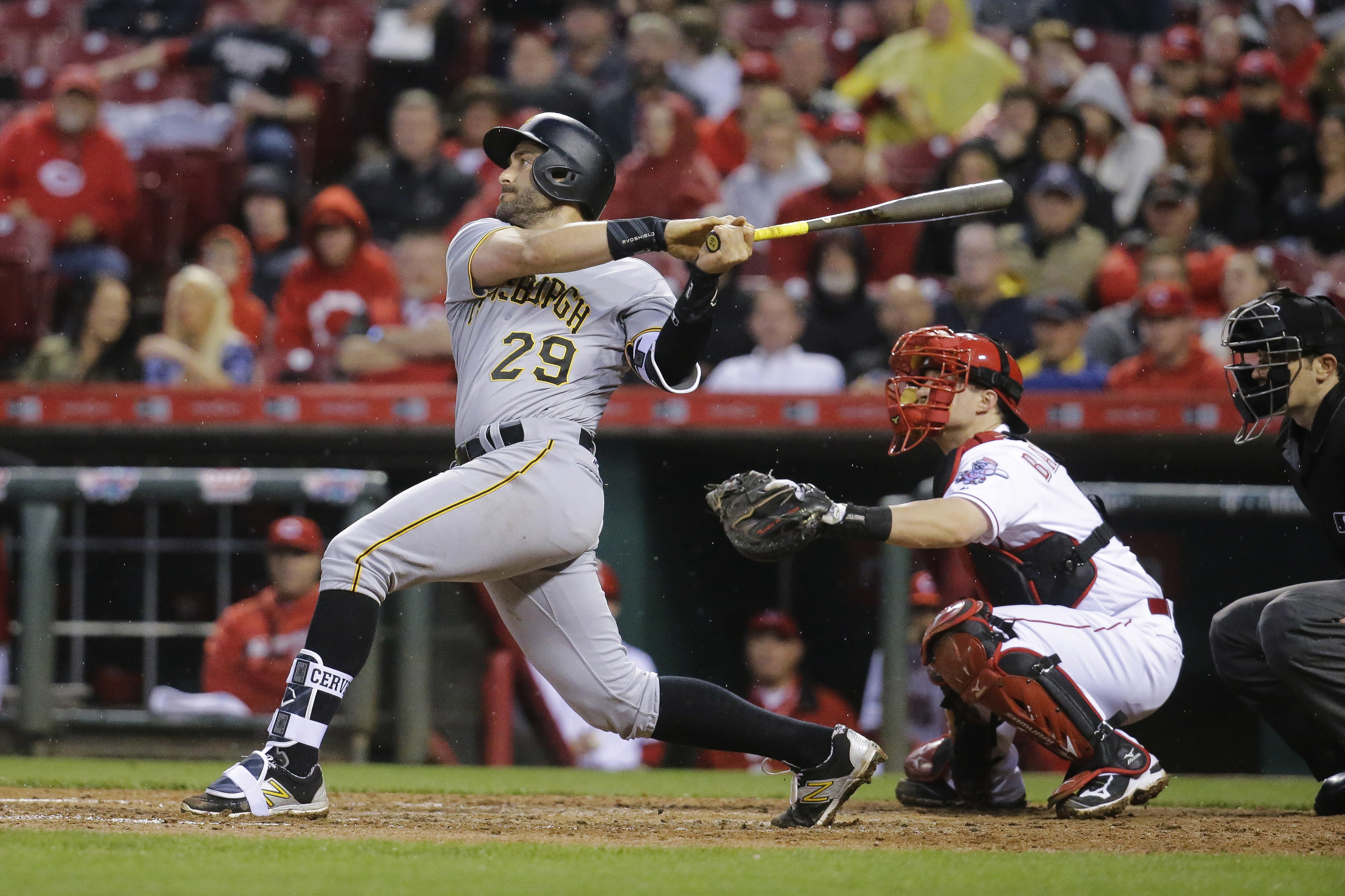 Pittsburgh Pirates' Francisco Cervelli (29) hits a RBI sacrifice fly off Cincinnati Reds relief pitcher Dan Straily to drive in Andrew McCutchen in the sixth inning of a baseball game, Monday, May 9, 2016, in Cincinnati. (AP Photo/John Minchillo)