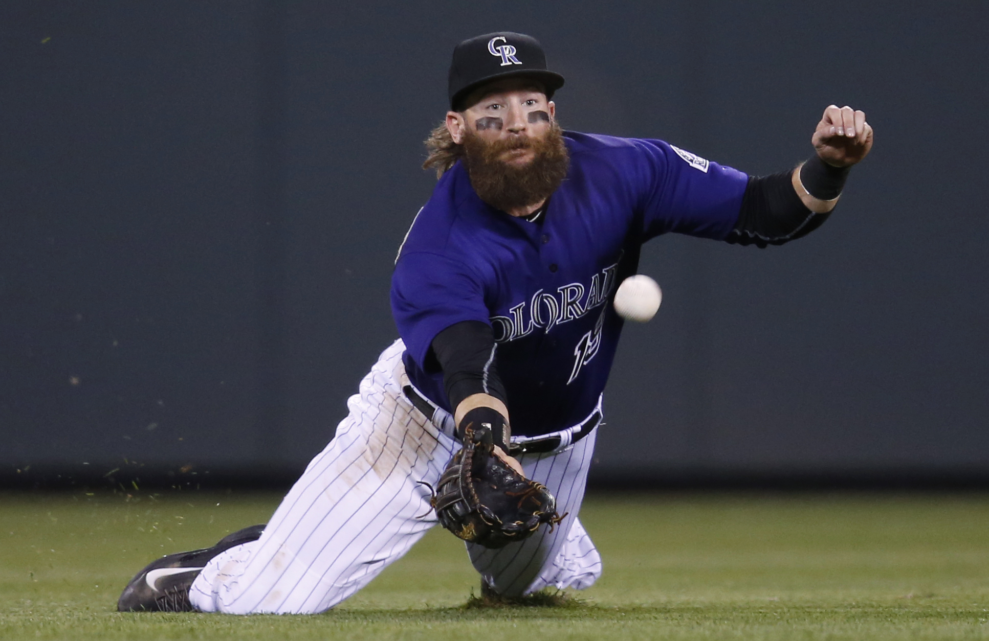 Colorado Rockies center fielder Charlie Blackmon dives but fails to field a double off the bat of Arizona Diamondbacks' Welington Castillo in the fifth inning of a baseball game, Monday, May 9, 2016, in Denver. (AP Photo/David Zalubowski)