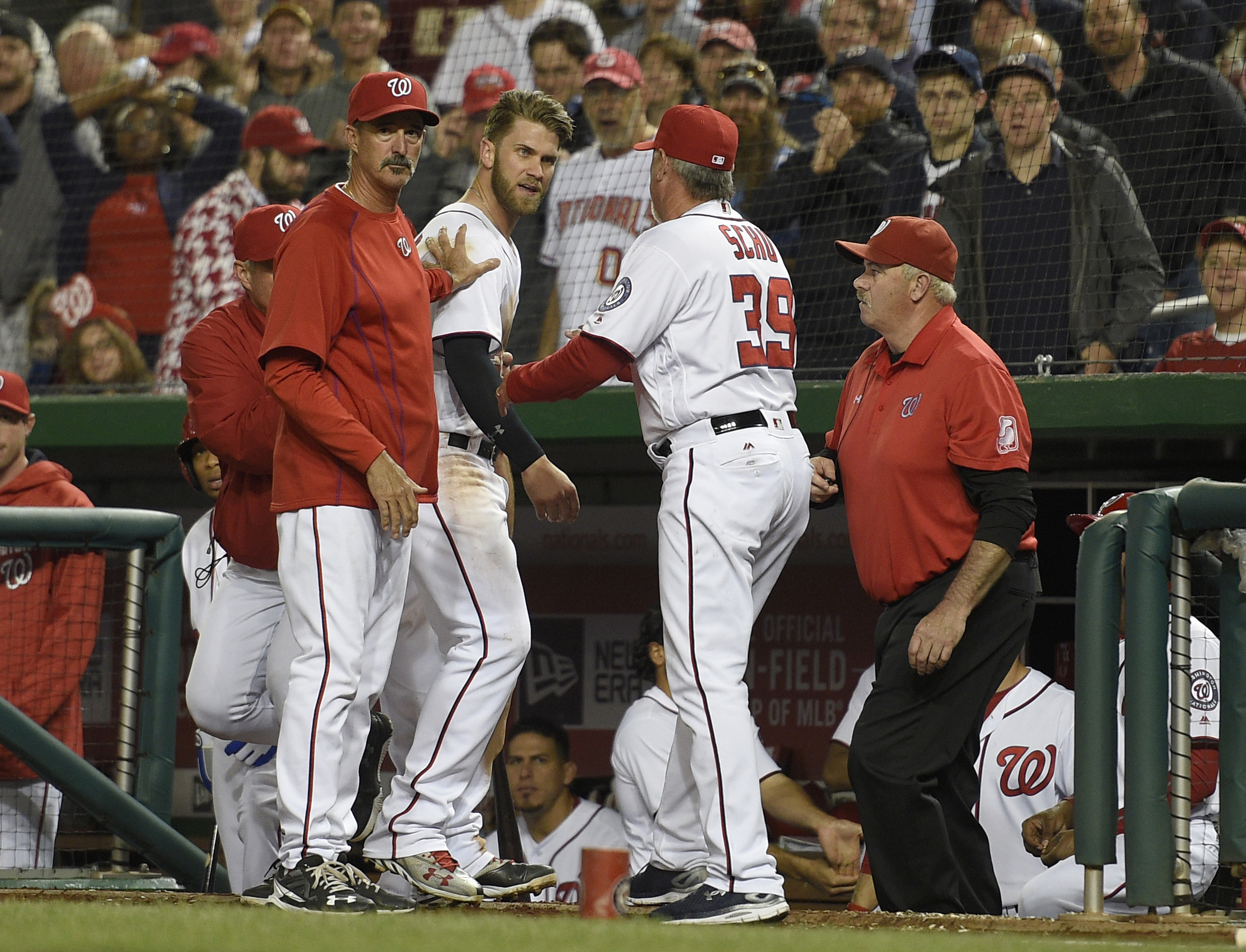 FILE - In this May 9, 2016 file photo, Washington Nationals' Bryce Harper, center, is restrained by pitching coach Mike Maddux, left, and hitting coach Rick Schu (39) after Harper was ejected in the dugout during the ninth inning of an interleague basebal