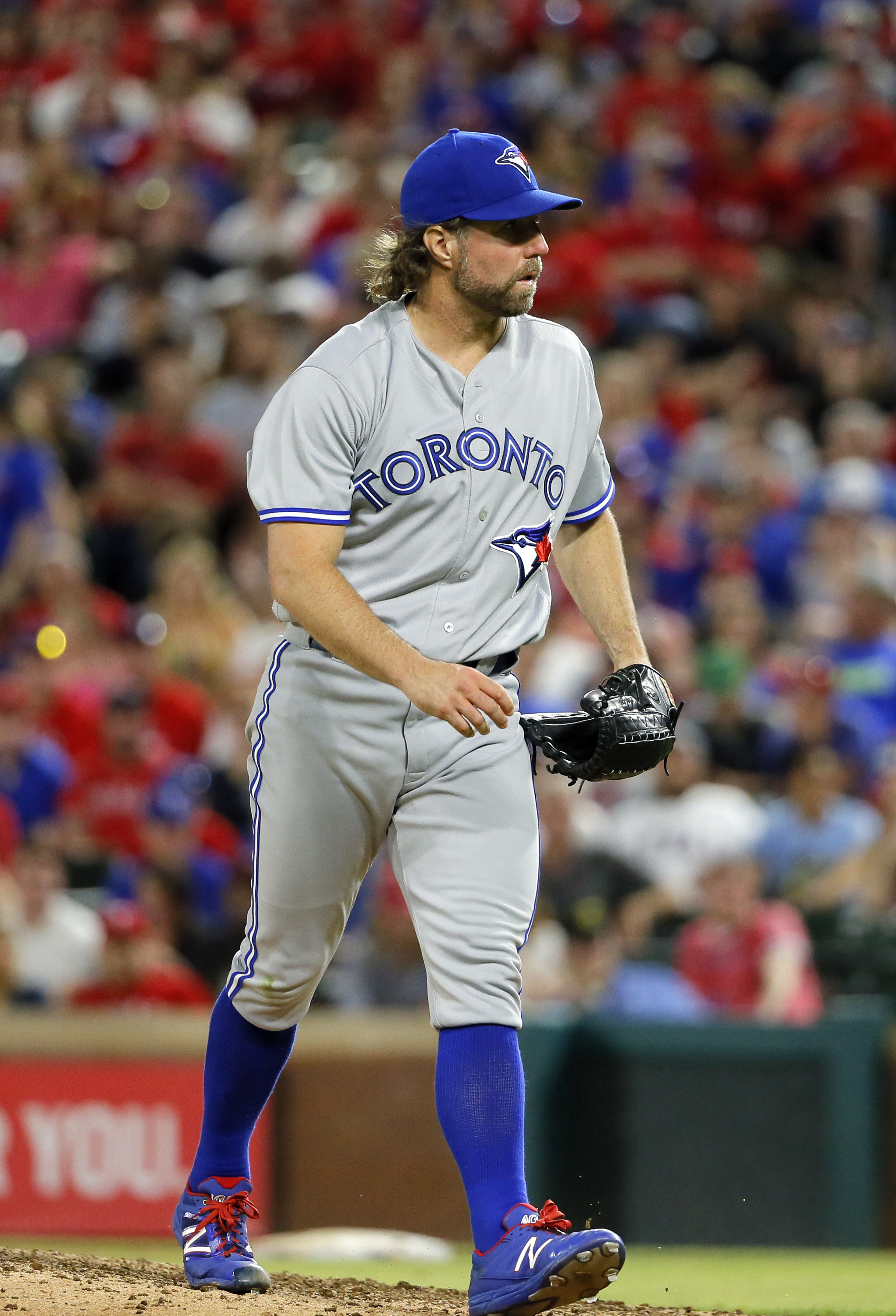 Toronto Blue Jays starting pitcher R.A. Dickey walks off the mound after getting the final out against the Texas Rangers in the seventh inning of a baseball game Friday, May 13, 2016, in Arlington, Texas. (AP Photo/Tony Gutierrez)